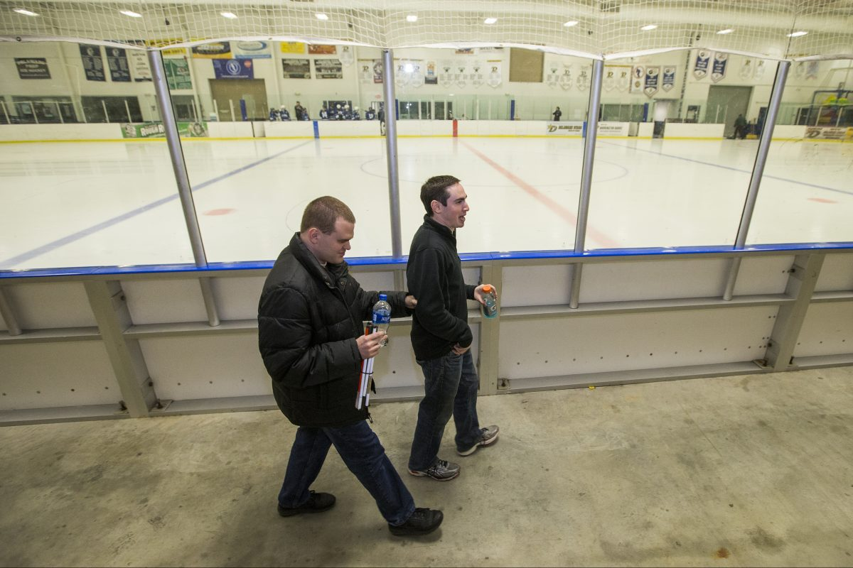 Matt Wallace, left, is color commentator to his play-by-play broadcast partner Sam Fryman, right, during University of Pennsylvania women's ice hockey games. Matt has been blind since birth.  The Temple grads walk by the rink before a recent game between Penn and Villanova on Feb. 16, 2018. CHARLES FOX / Staff Photographer