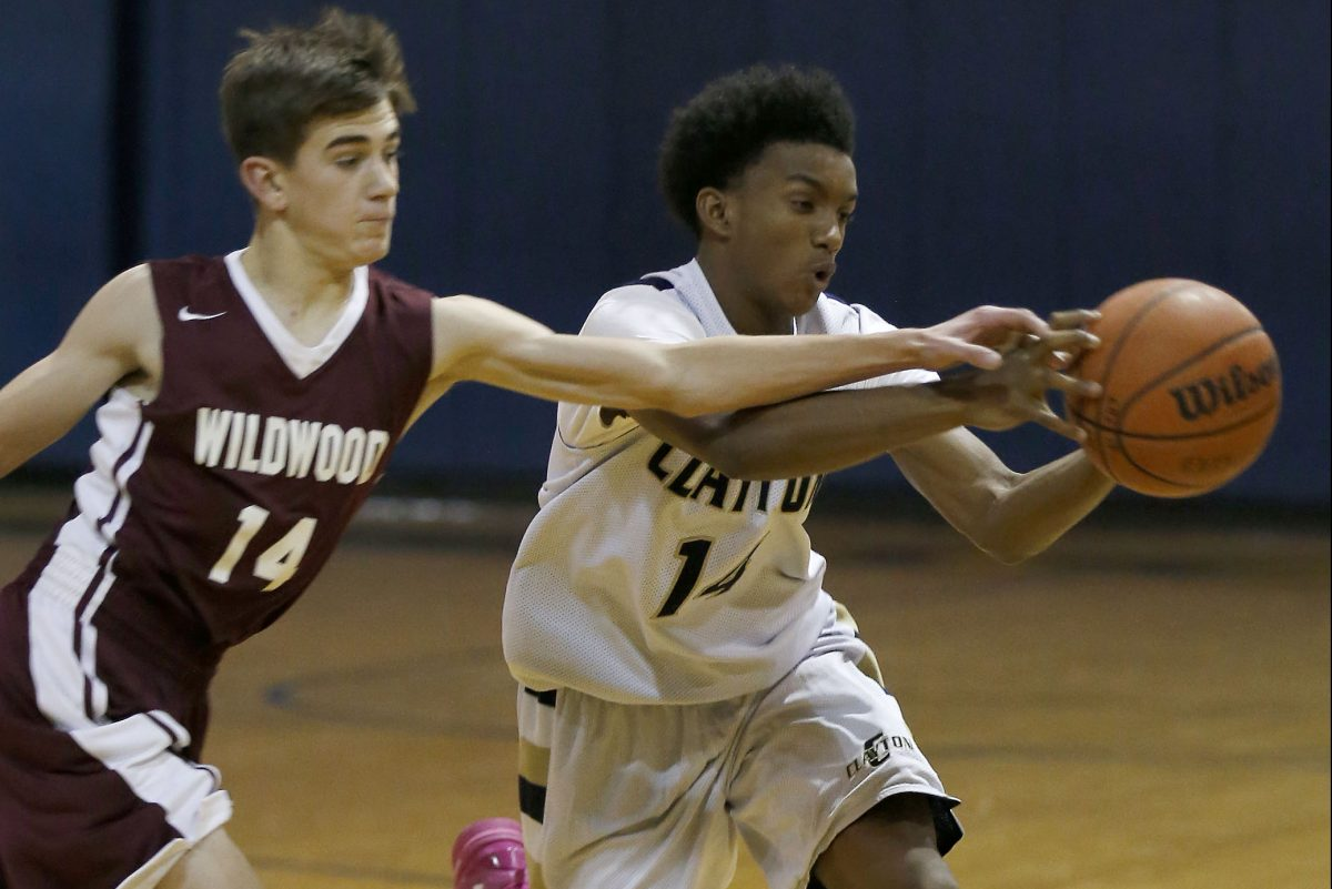 Clayton High';s Solomon Robinson (right) catches the basketball against Wildwood High's Tyler Tomlin during the first-quarter on Monday, December 19, 2016.