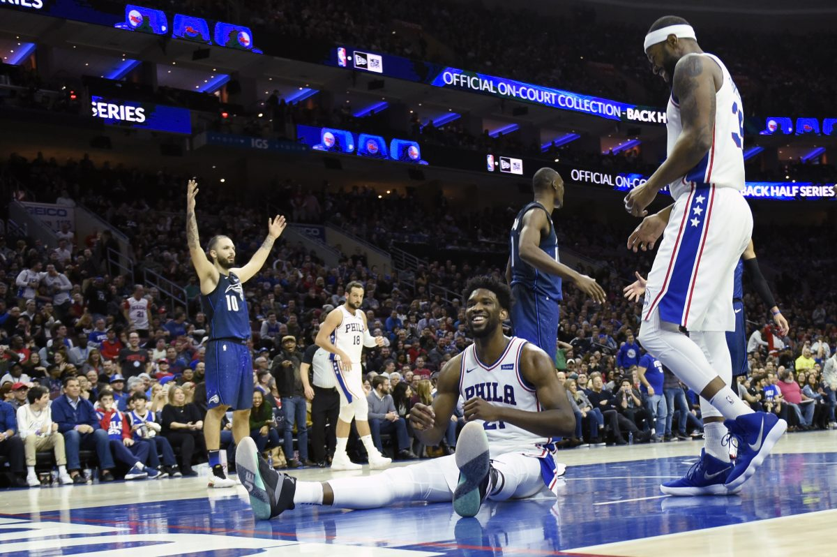 Sixers center Joel Embiid laughs after getting fouled on a dunk attempt during the Sixers' win over the Magic on Saturday.