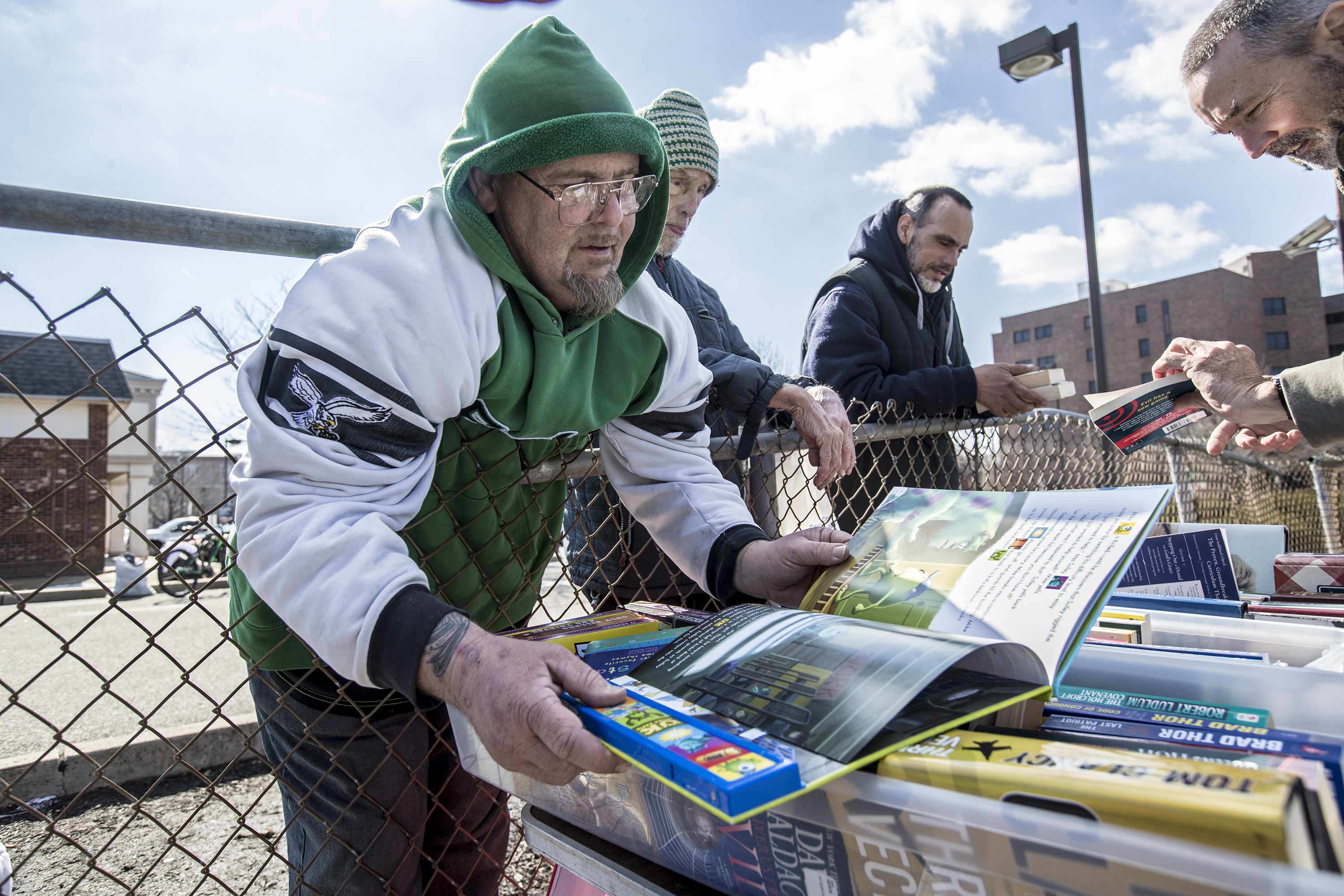 Tank B., left, a homeless man in Camden, NJ, leans over the fence to look over a book that he was going to pick up for his 3 1/2 year old daughter, at the Pop-Up Library that Tom Martin, right, regularly sets up in downtown Camden.