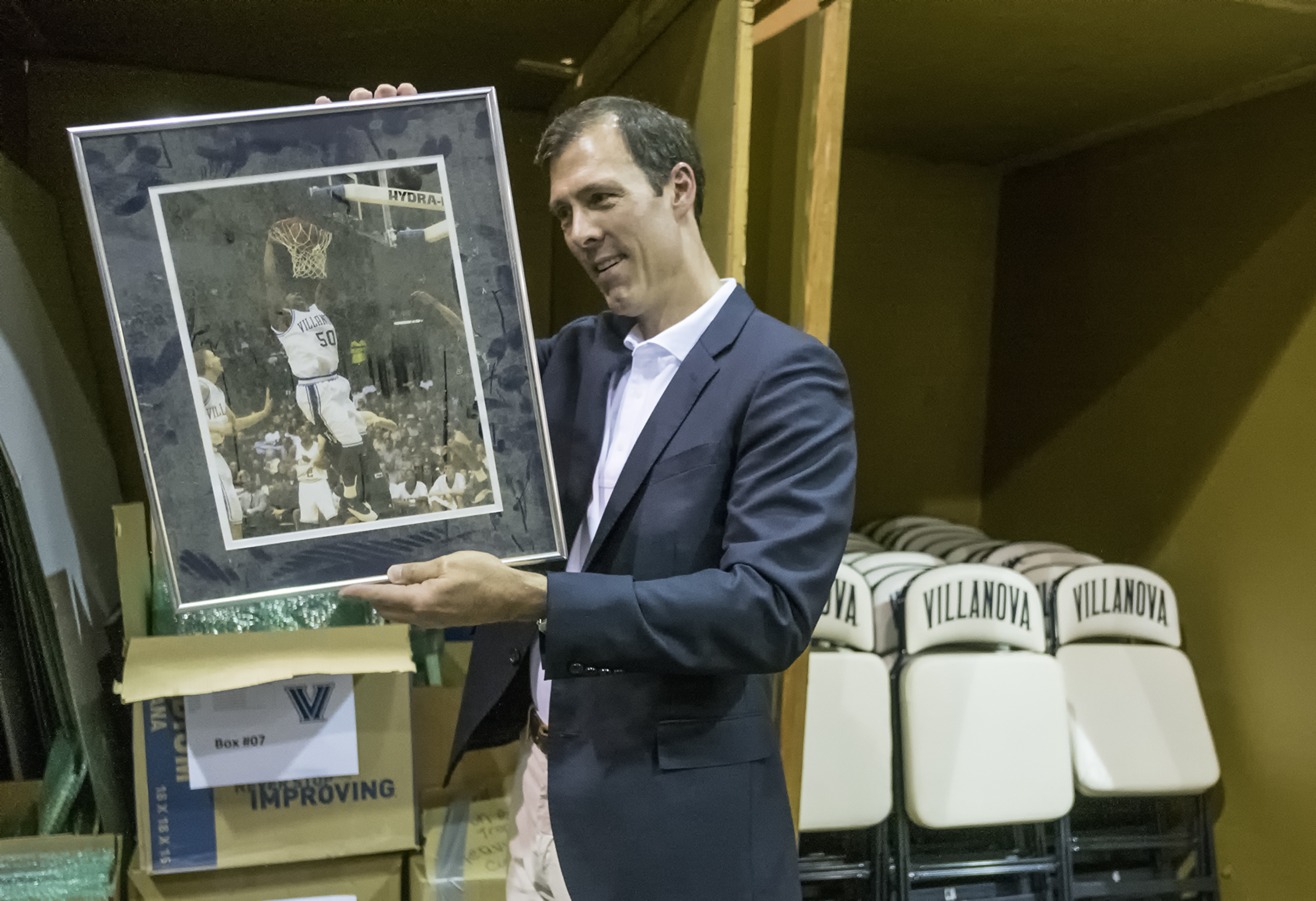 Scott Reidenbach, at his King of Prussia warehouse, looks over a photograph of Will Sheridan dunking against Temple.