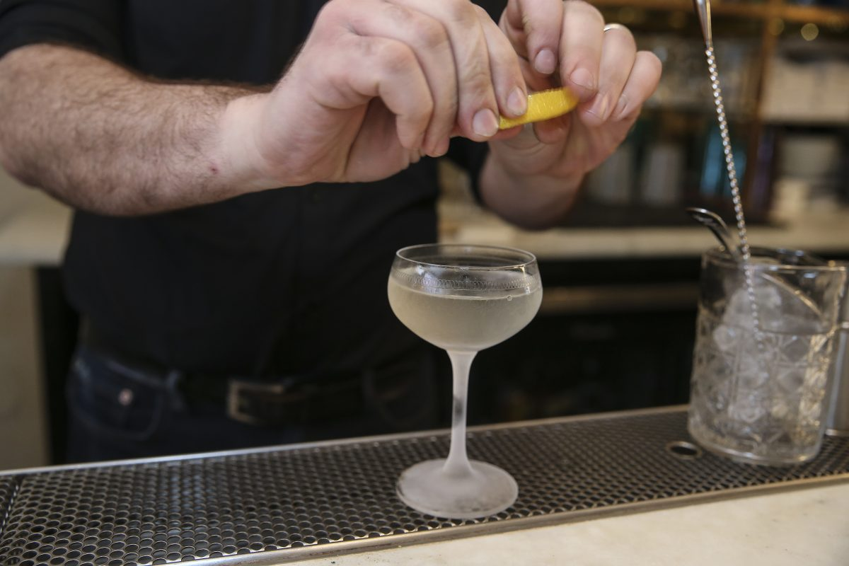 Bartender Paul MacDonald adds the lemon to a sherry martini at Friday Saturday Sunday.