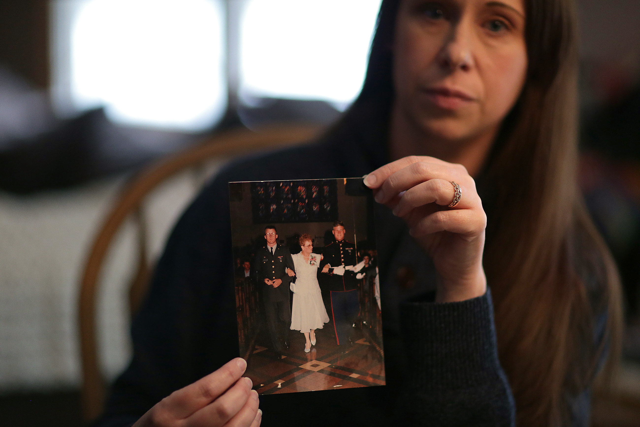 Courtney Bracken holds a family photo of her deceased boyfriend, Robert Dickson, at left in the photo, in Mantua NJ on March 1, 2018. Robert died of a heroin overdose in the Kensington section of Philadelphia in December 2017. In the family photo are Robert, his mother, Pat, and brother, Billy. He was found overdosed in a Kensington breezeway with only an army tattoo to help investigators eventually identify him.