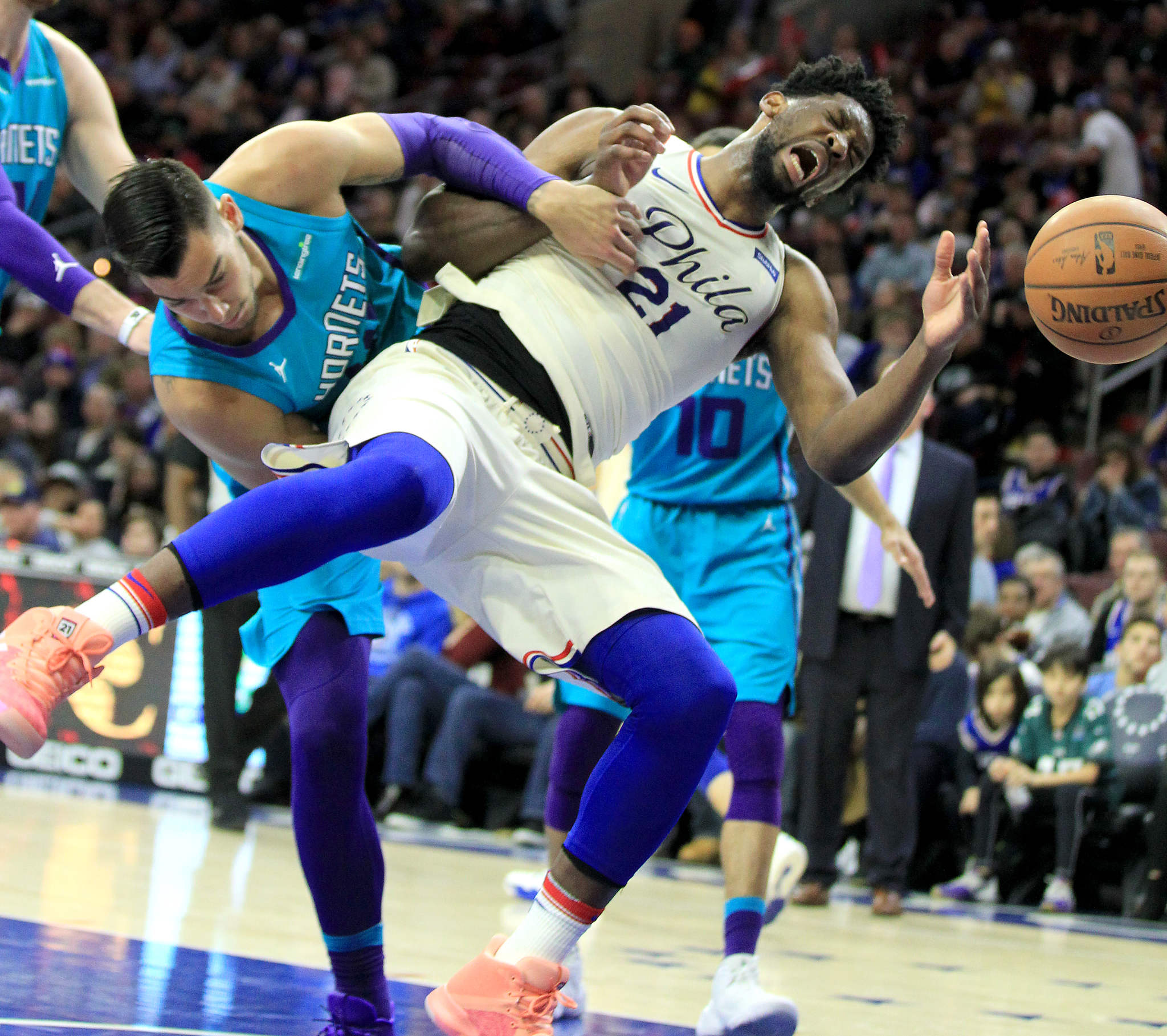 Joel Embiid, right, of the Sixers gets fouled hard by Willy Hernangomez of the Hornets during the 3rd quarter at the Wells Fargo Center on March 2, 2018.