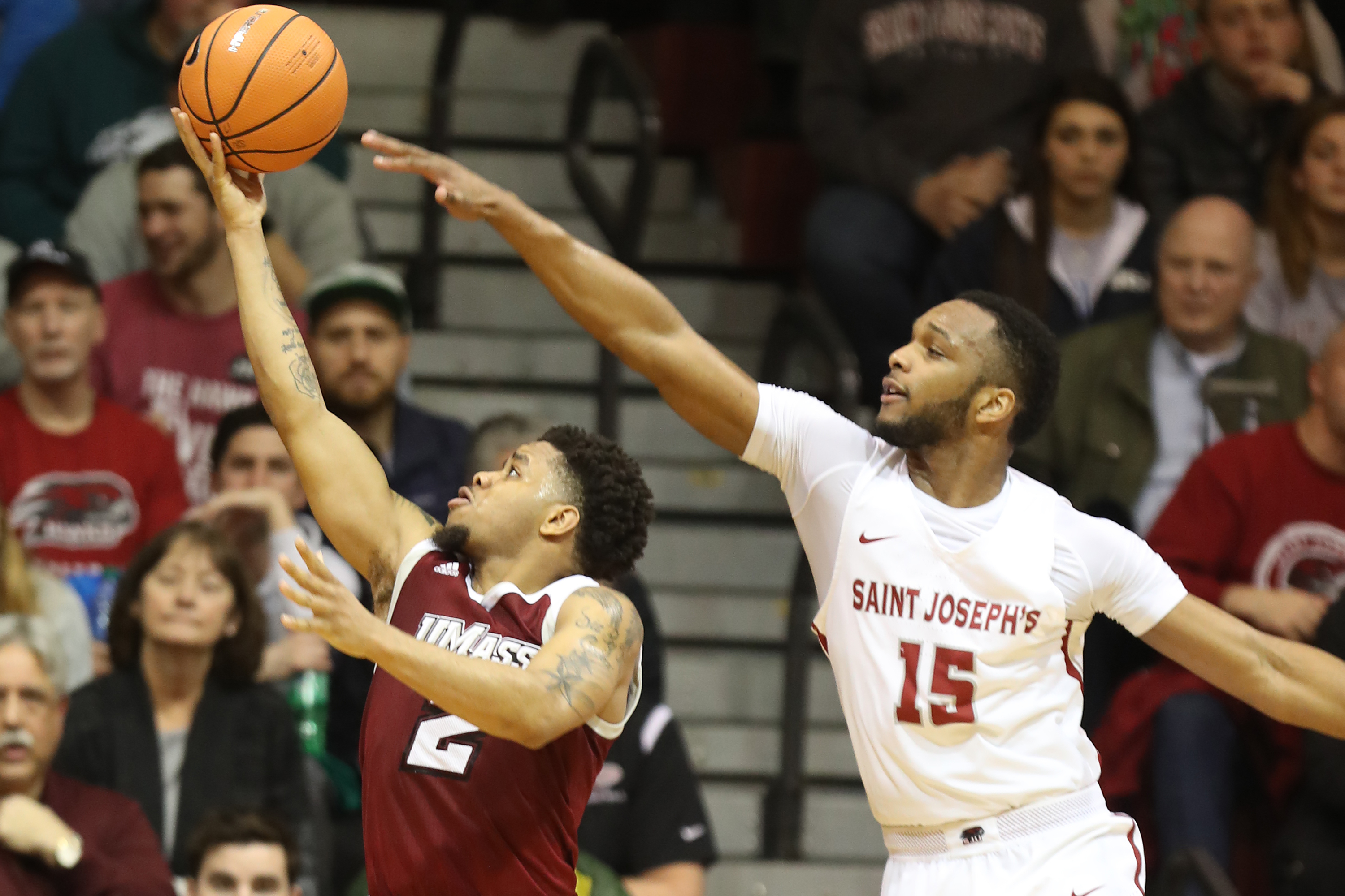 Chris Clover, right, of St. Joseph's barely misses blocking a shot by Luwane Pipkins of Massachusetts during the 2nd half at Hagan Arena on Feb. 10, 2018. CHARLES FOX / Staff Photographer