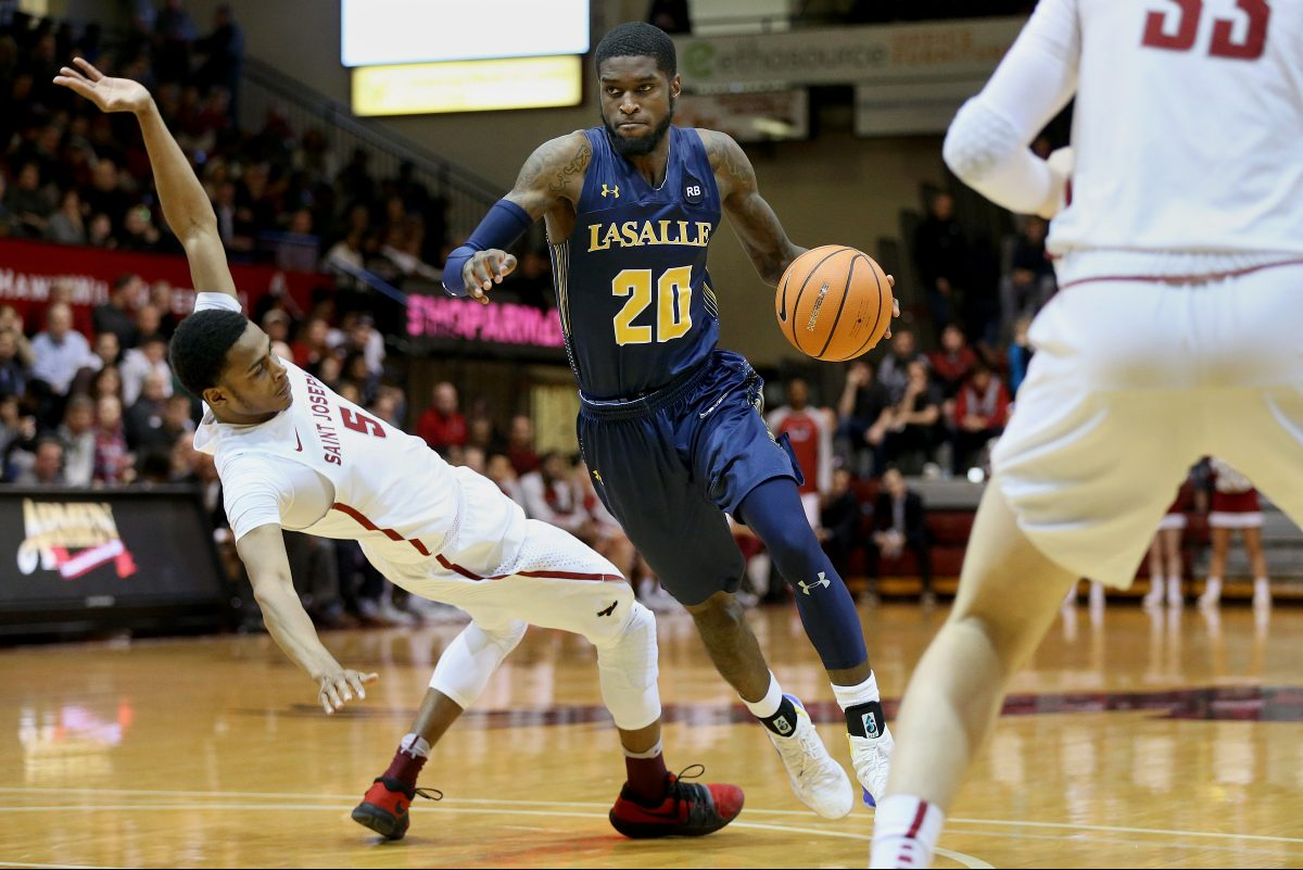 La Salle's B.J. Johnson (right) drives past Saint Joseph's Nick Robinson during a game at Hagan Arena on Saturday.