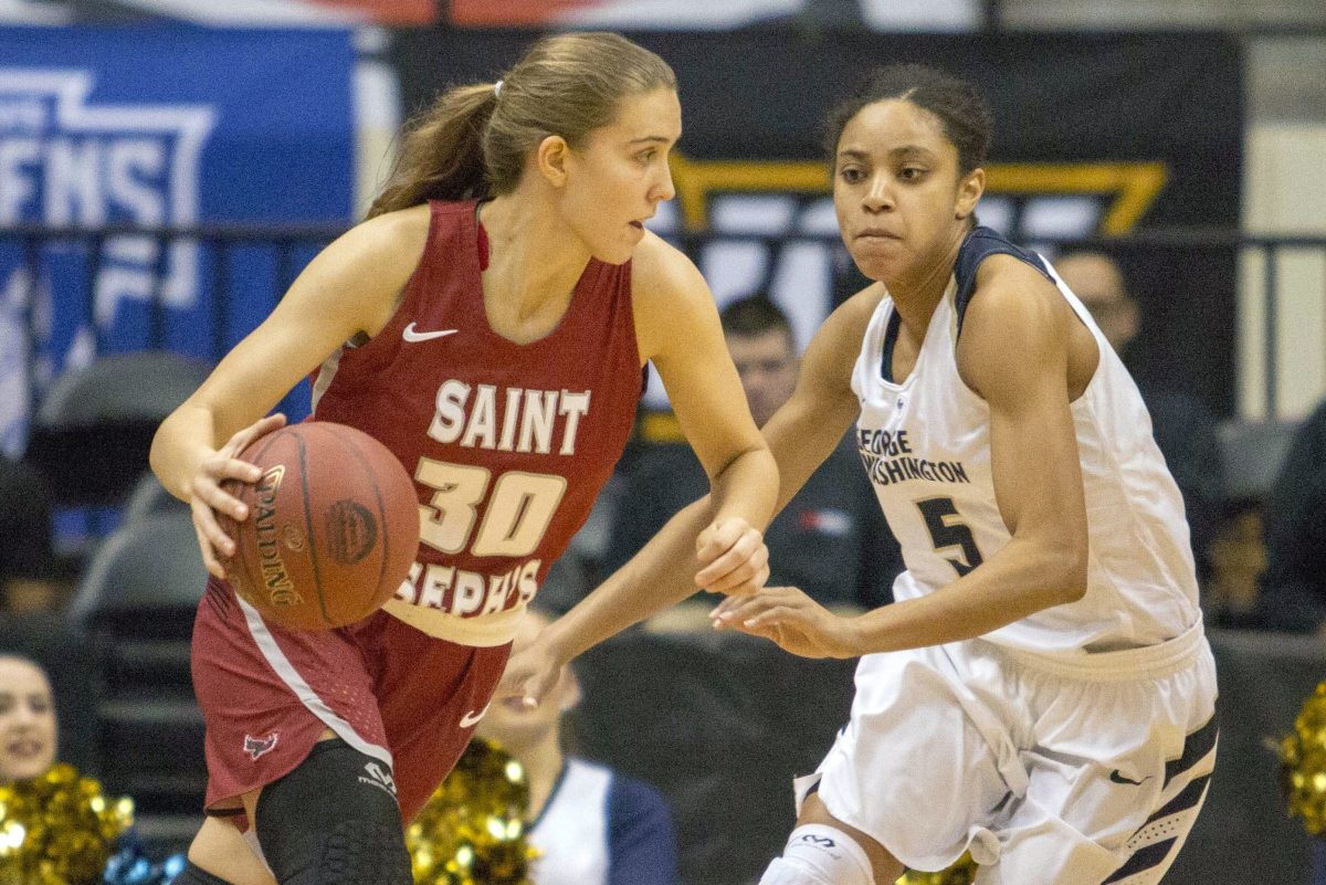 Saint Joseph´s Sarah Veilleux  finds an opening against George Washington guard Brianna Cummings during the Atlantic Ten final.