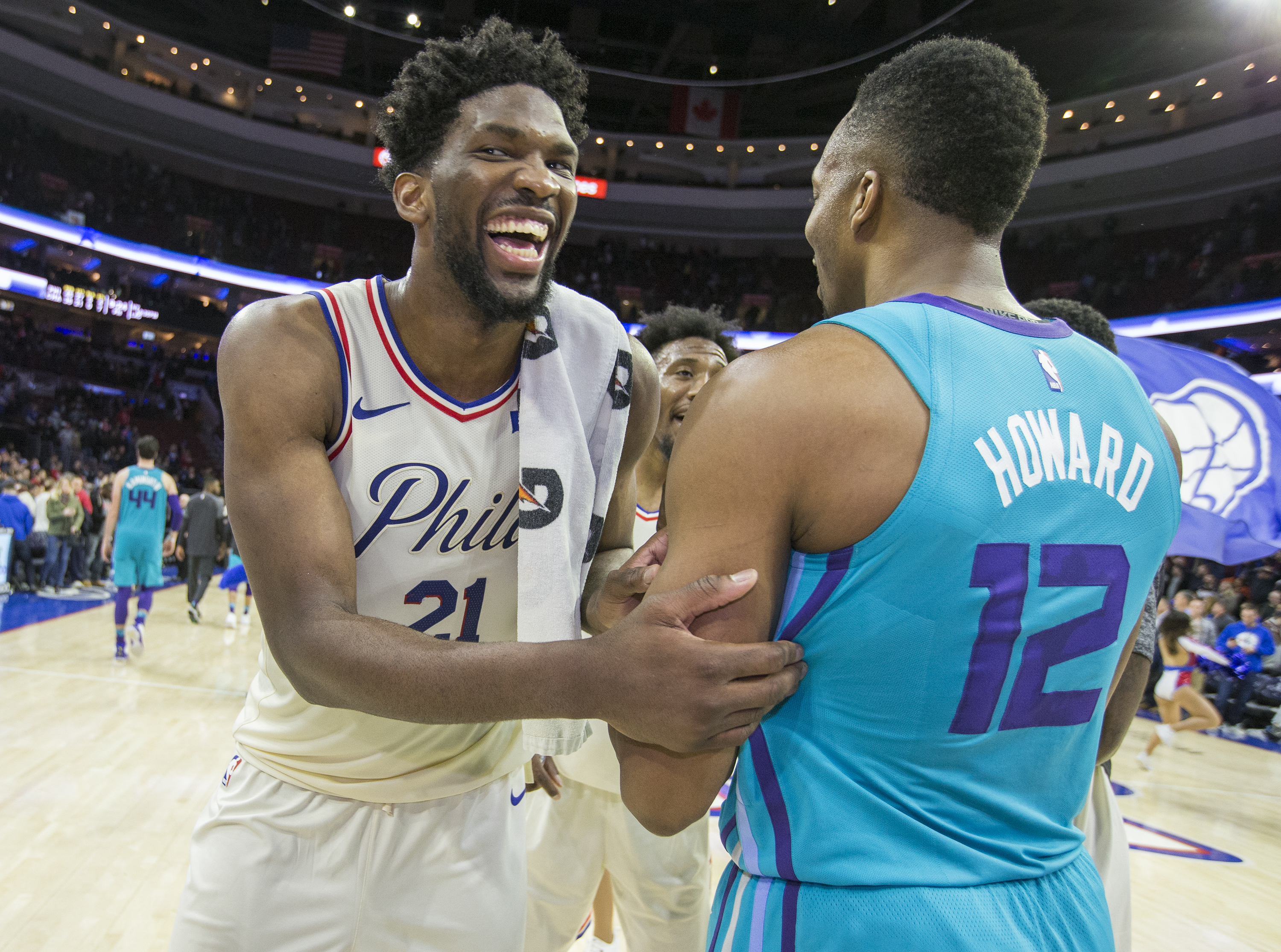 Joel Embiid, left, jokes with Dwight Howard of the Hornets after their game at the Wells Fargo Center on March 2.