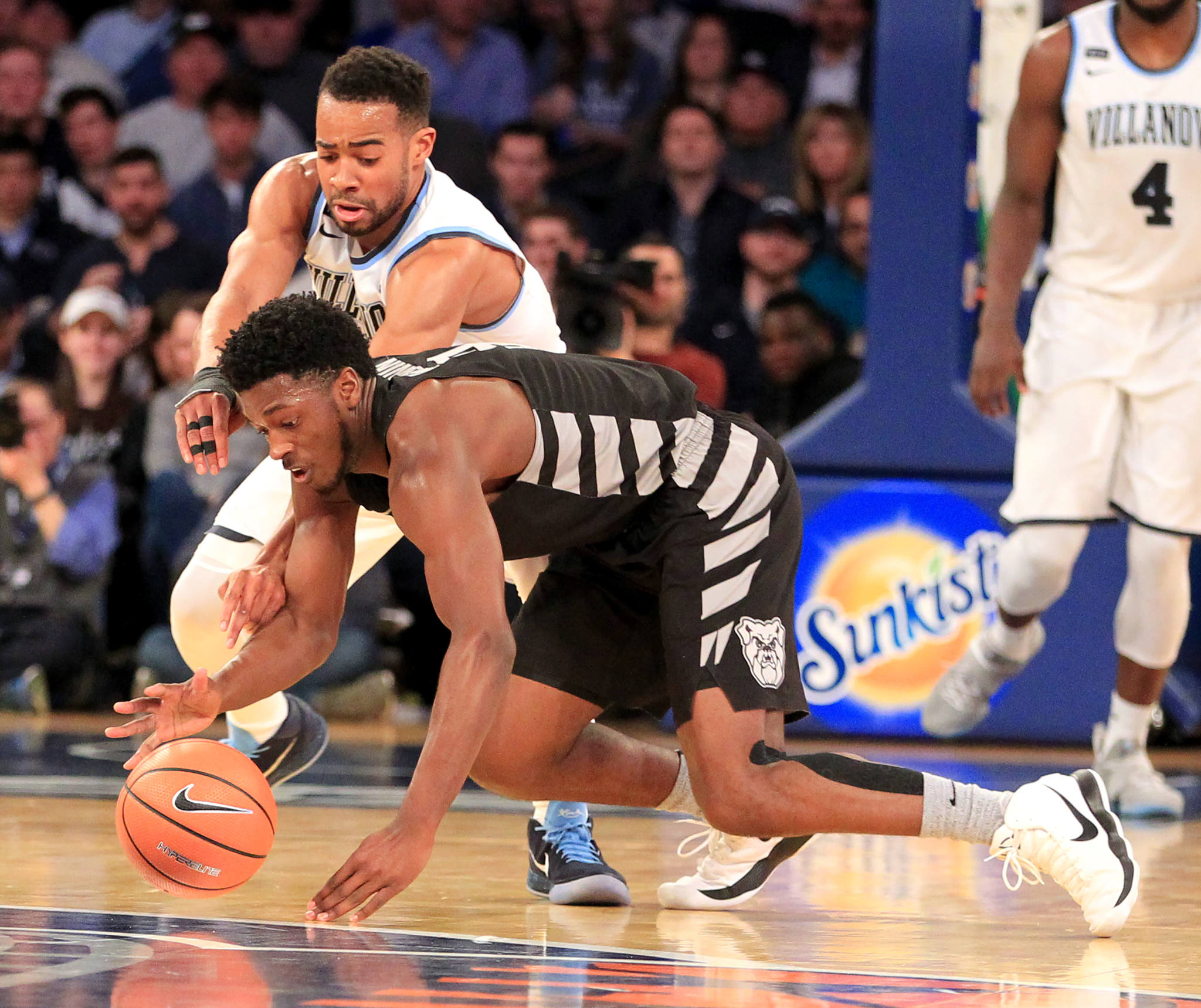 Phil Booth, top, of Villanova and Kamar Baldwin of Butler scramble For a loose ball during the 2nd half in the Big East Tournament semi-finals at Madison Square Garden on March 9, 2018.