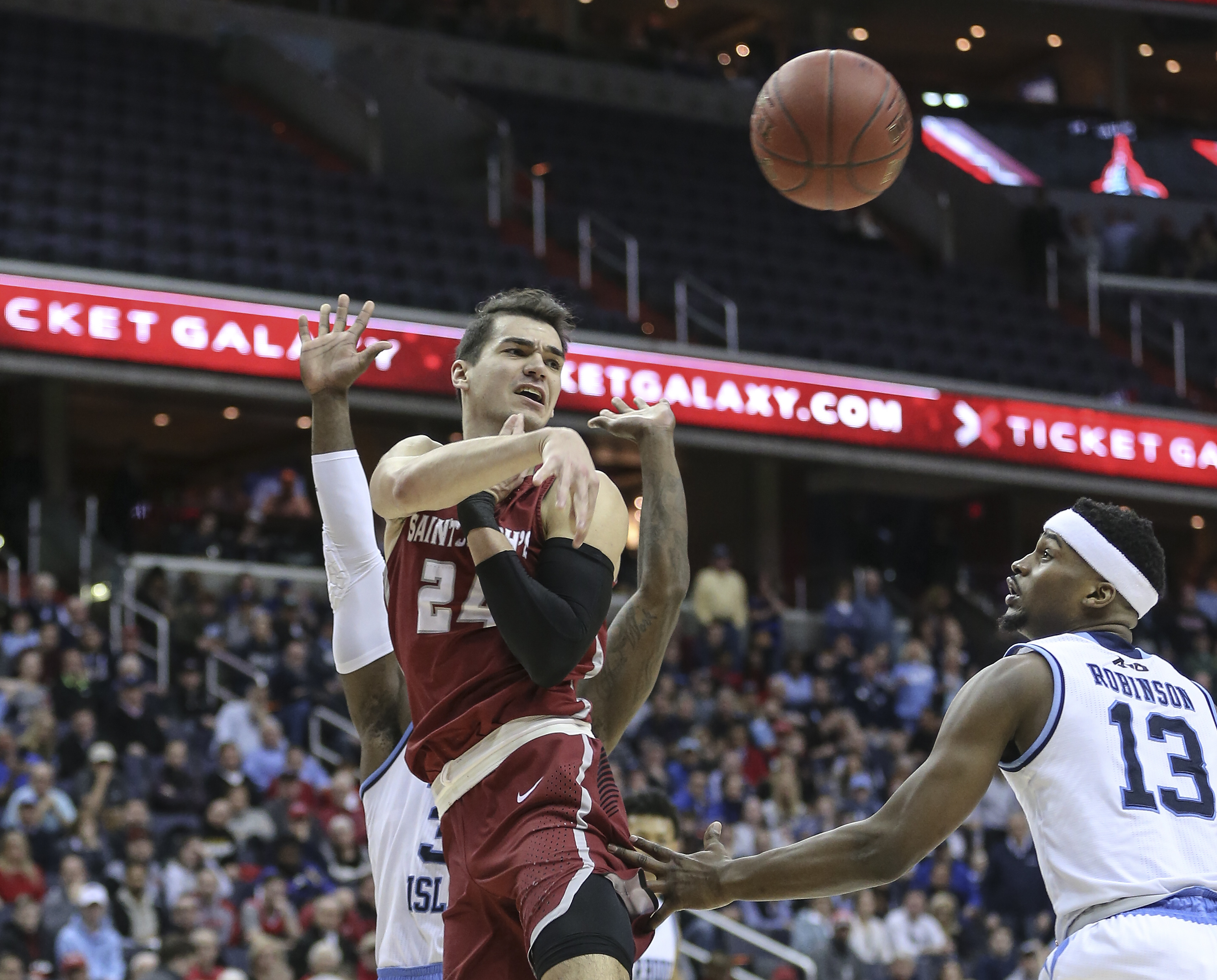 St. Joseph´s forward Pierfrancesco Oliva throws a pass over Rhode Island´s guard Stanford Robinson during the 2nd half of the A-10 tournament, semifinals, at the Capital One Arena, in Washington, DC, Saturday, March 10, 2018. Rhode Island beats St. Joes 90-87 to advance to the Finals. STEVEN M. FALK / Staff Photographer