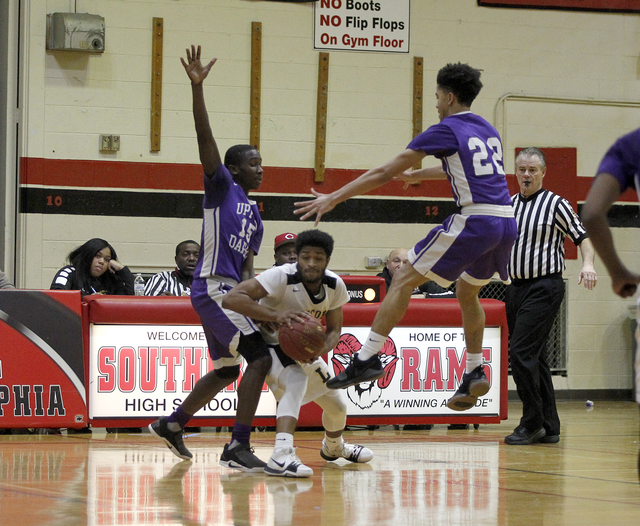 Lincoln´s Emeuel Charleston (center) looks to pass as Upper Darby´s Diby Keita (15) and Phil Williams (22) defend.