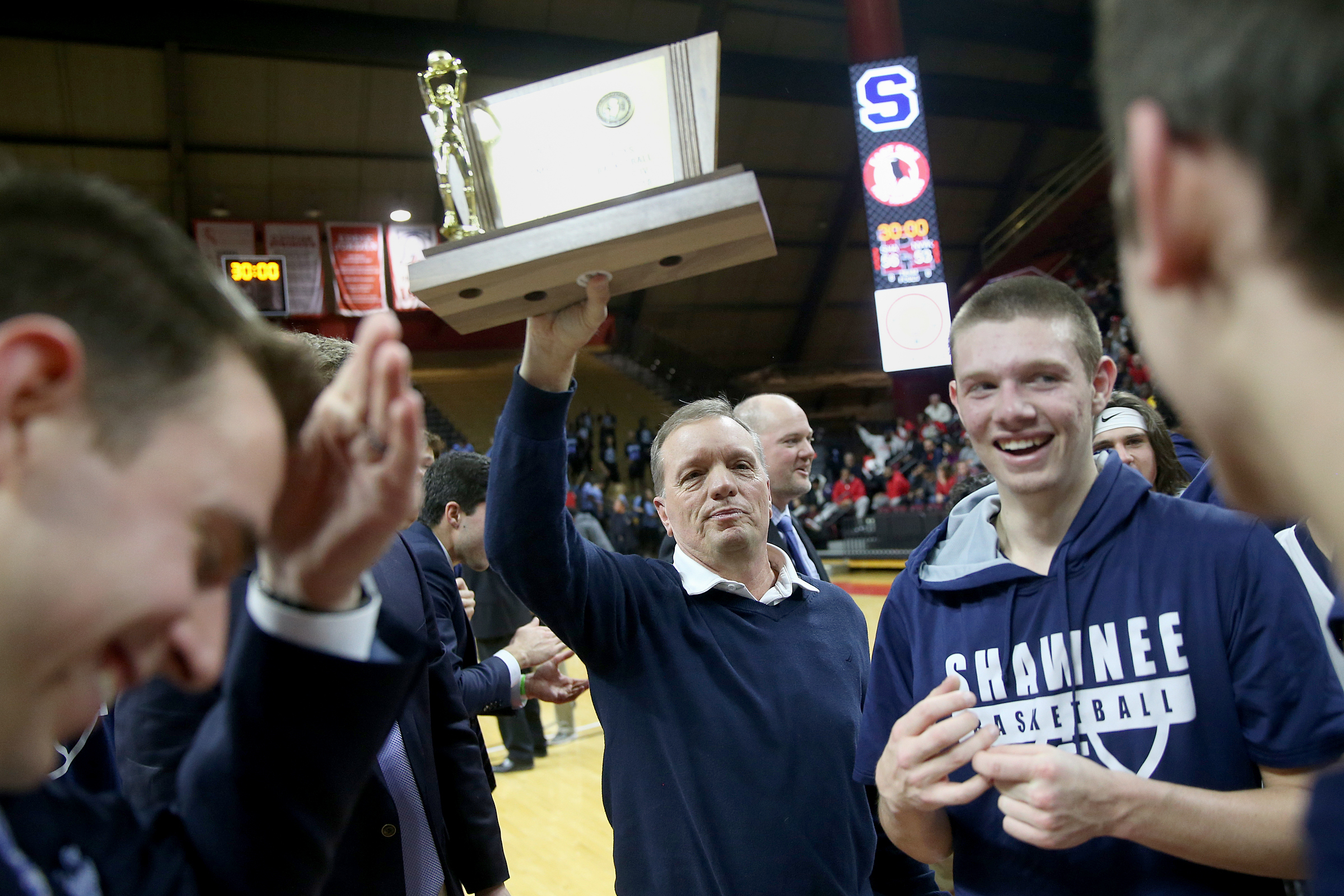 Shawnee head coach Joe Kessler and his players celebrate with the trophy after the Group 4 state championship game against Newark East Side at the Louis Brown Athletic Center.