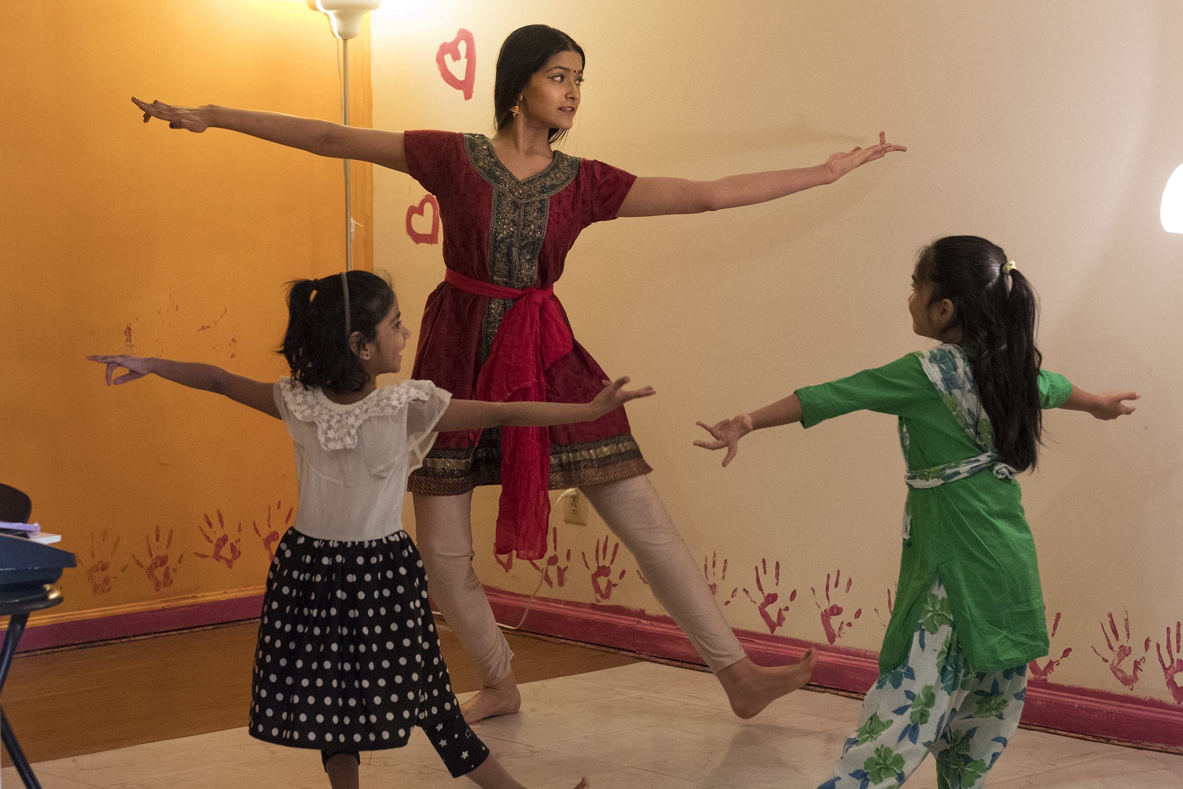 Ashraya Ananthanarayanan, 17, a senior at Commonwealth Charter Academy, has already taken so many college-level classes at Harvard that when she arrives on the Cambridge, Massachusetts, campus as a full-time student in September she will be considered a senior. Here, she teaches a class on traditional Indian dancing to two 7 year olds - Shamuyuktha Sunsararajan, left and Avika Ka;e, right.( ED HILLE / Special to the Inquirer.)