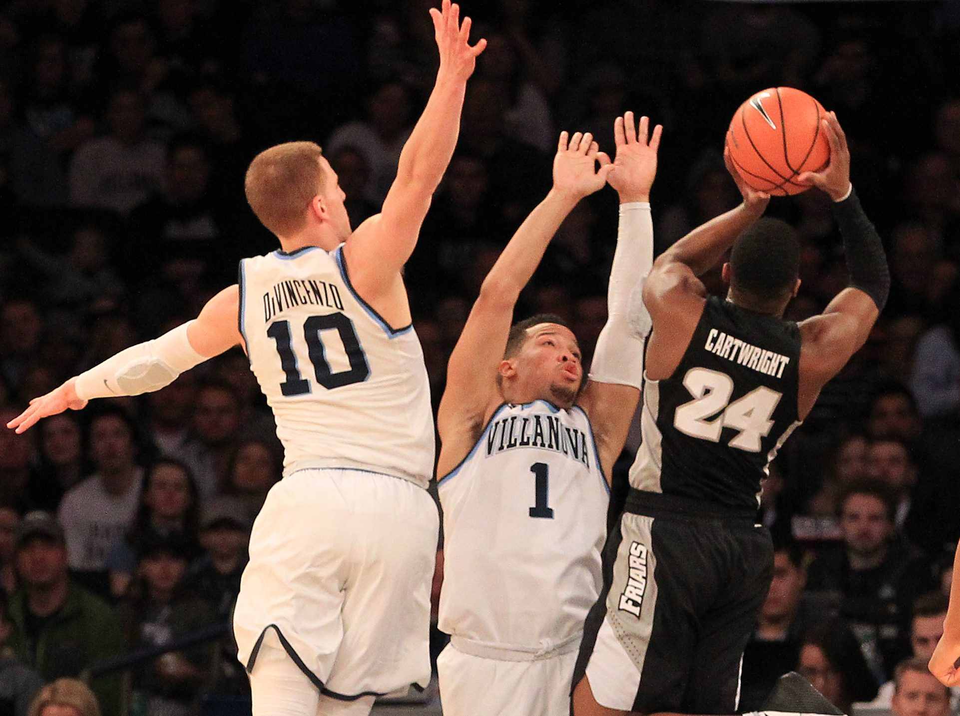 Jalen Brunson (1) and teammate Donte DiVincenzo try to stop a shot by Kyron Cartwright of Providence during the the Big East tournament final.