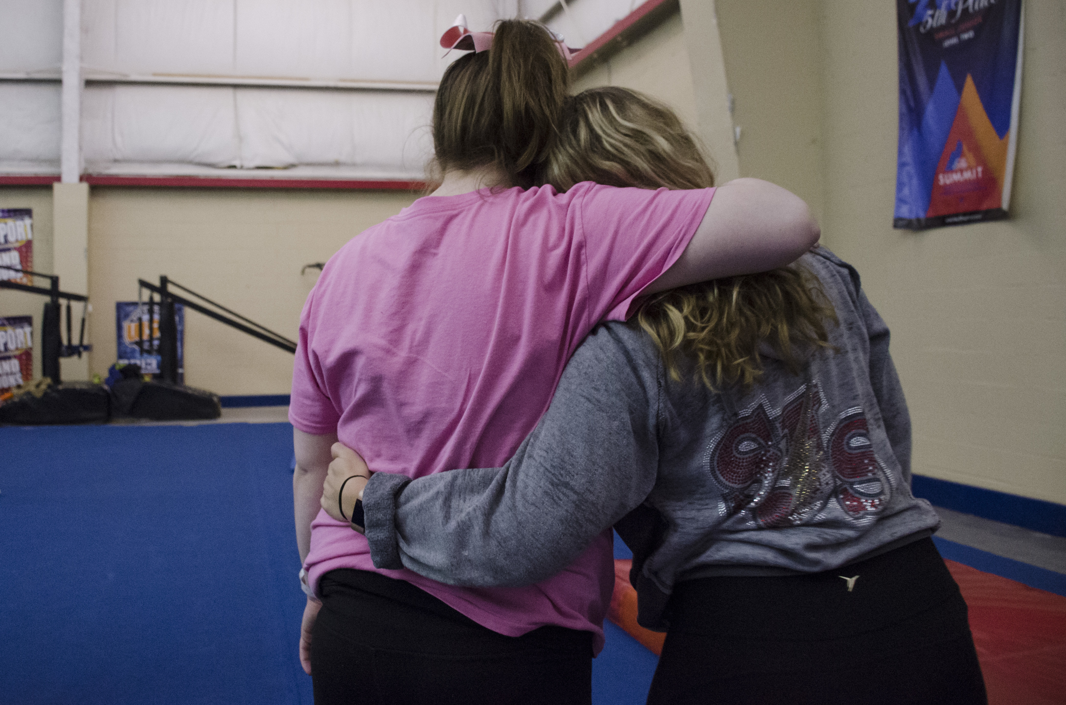 """Morgan Borner, left, hugs her coach, Michelle Nolan, right, during practice at the South Jersey Storm practice facility in Sewell, Pa., on Wednesday, March 14, 2018. The """"Twisters"""" are one of only 5 special needs teams across the country to win a bid to the United States All-Star Federation 2018 Cheerleading and Dance World Championships in Orlando. ( CAMERON HART / For the Inquirer )"""