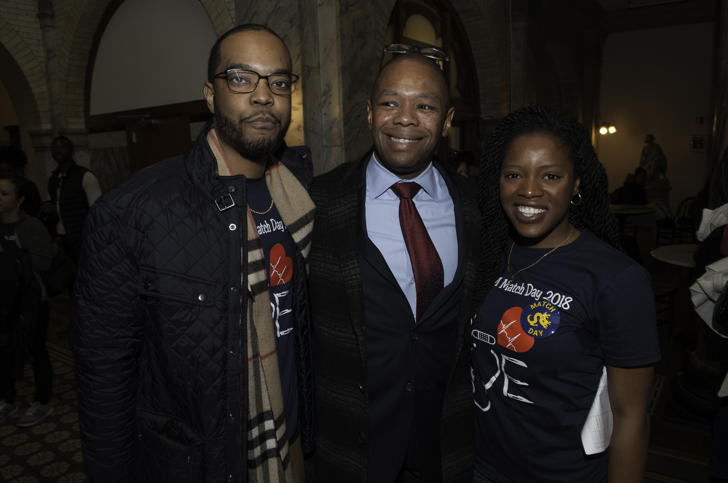 Medical students Dexter Graves (left), and Bisola Egbe (right) celebrate at medical student Match Day with Dr. Ted Corbin (center), who served as adviser to their network. (RAYMOND W HOLMAN JR / For the Philadelphia Inquirer )