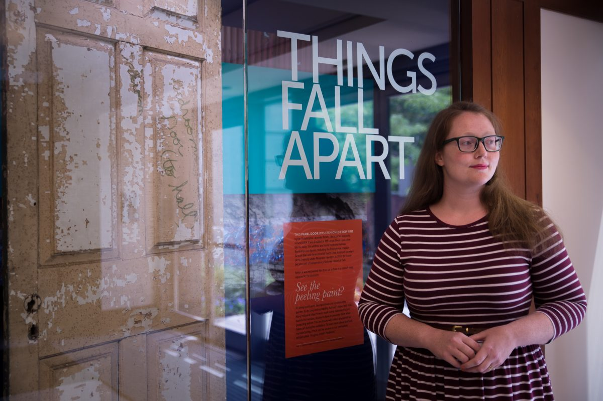 "Curator Elisabeth Berry Drago stands next to decaying doorway to exhibit ""Things Fall Apart."""