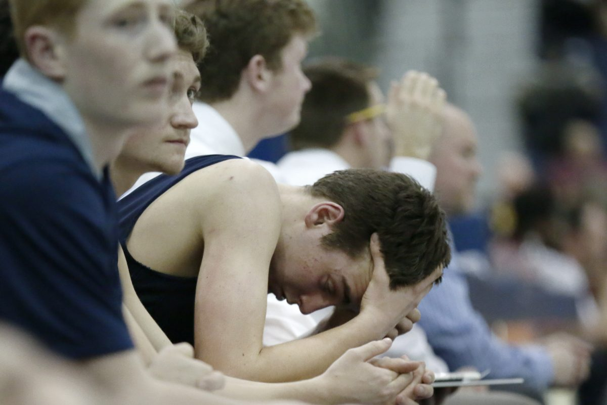 Shawnee's Kane Feudtner rests his head in his hands briefly after coming out of the game late in Shawnee's loss to Don Bosco prep.