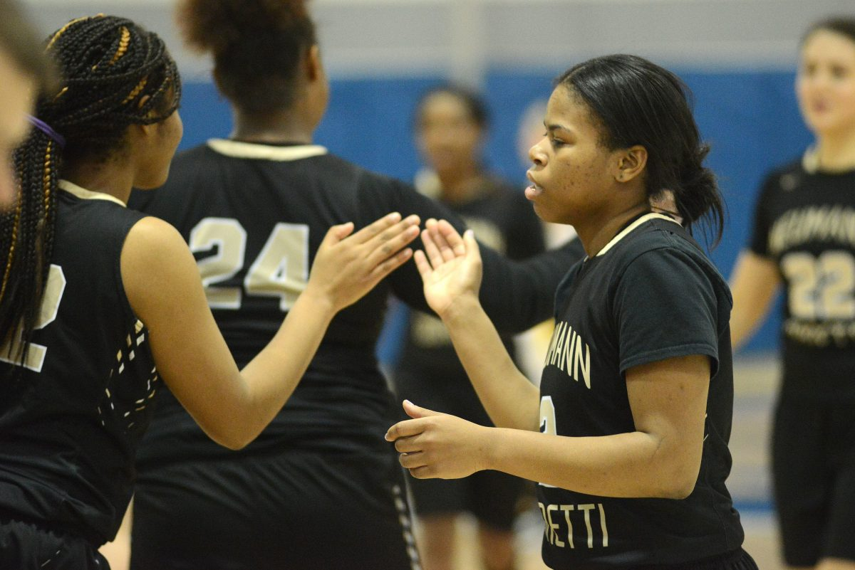 Neumann-Goretti's Angel Ricks (left) and Kiara Koger celebrate after defeating St. Basil Friday night.
