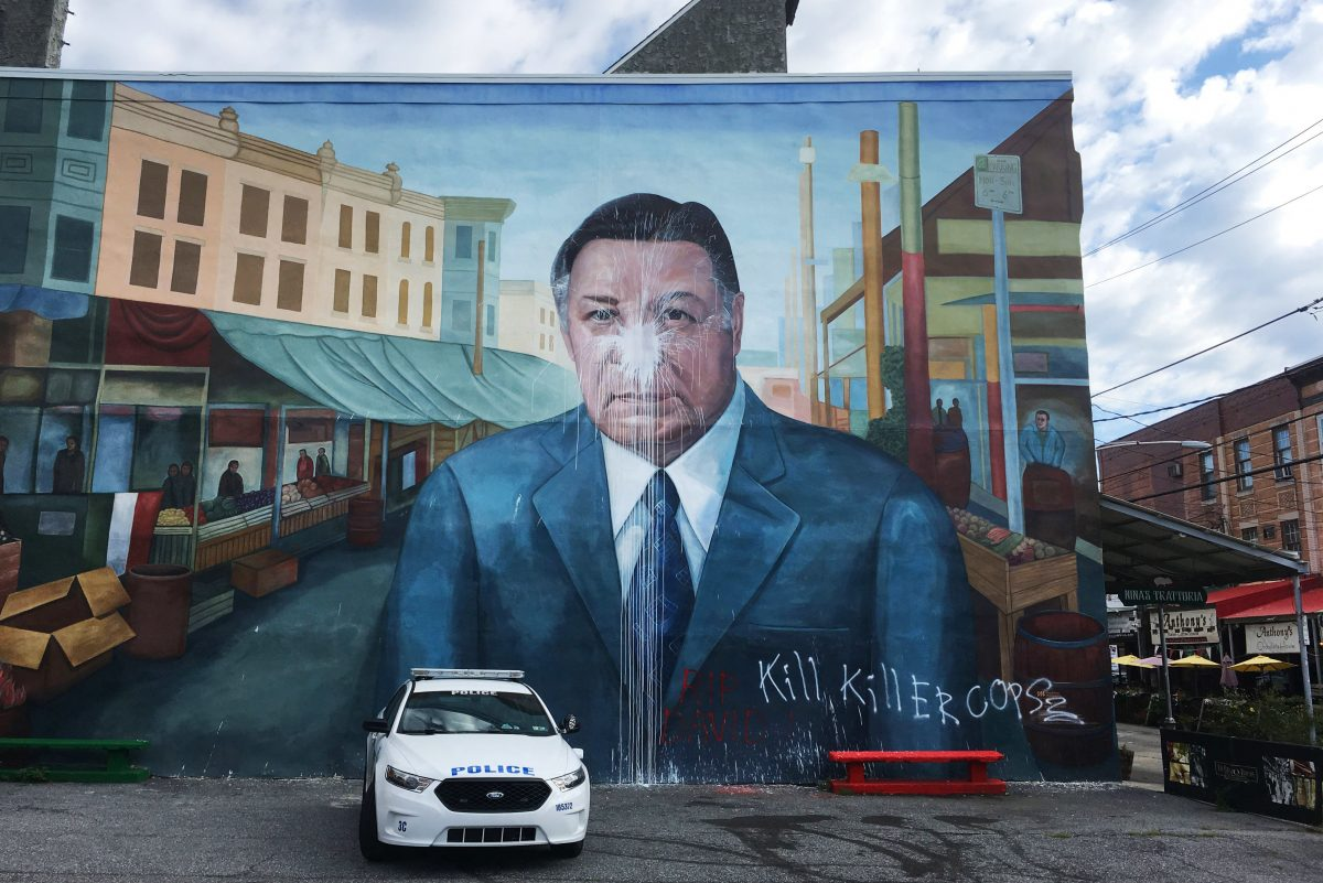 A police car is parked in front of the Frank Rizzo mural after it was vandalized in South Philadelphia in August.