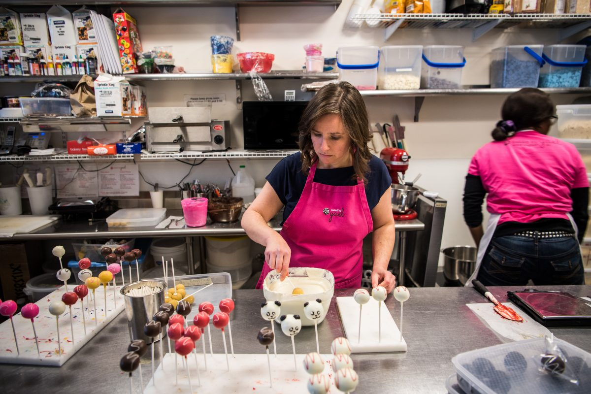Owner Yael Krigman dips cake pops at her shop Baked by Yael in Washington.