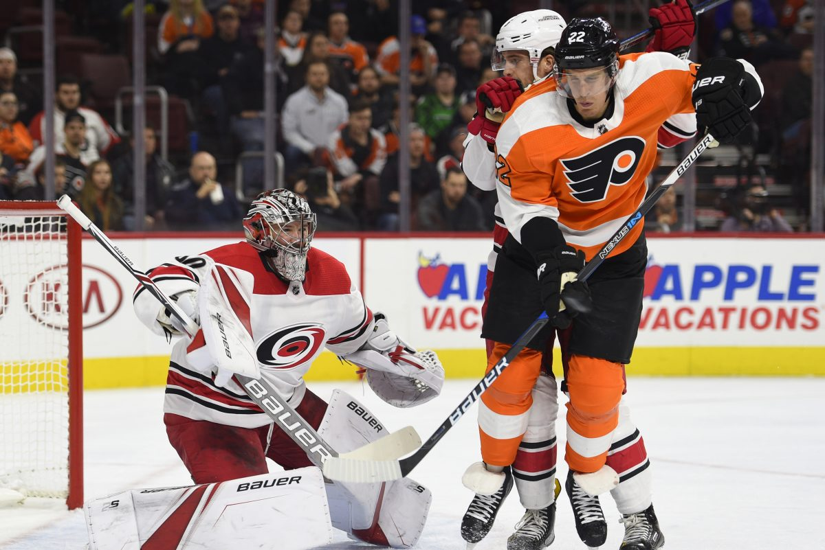 Hurricanes goalie Cam Ward looks for the puck behind a screen by Dale Weise during the second period of a March 1 game, which was won by visiting Carolina, 4-1.