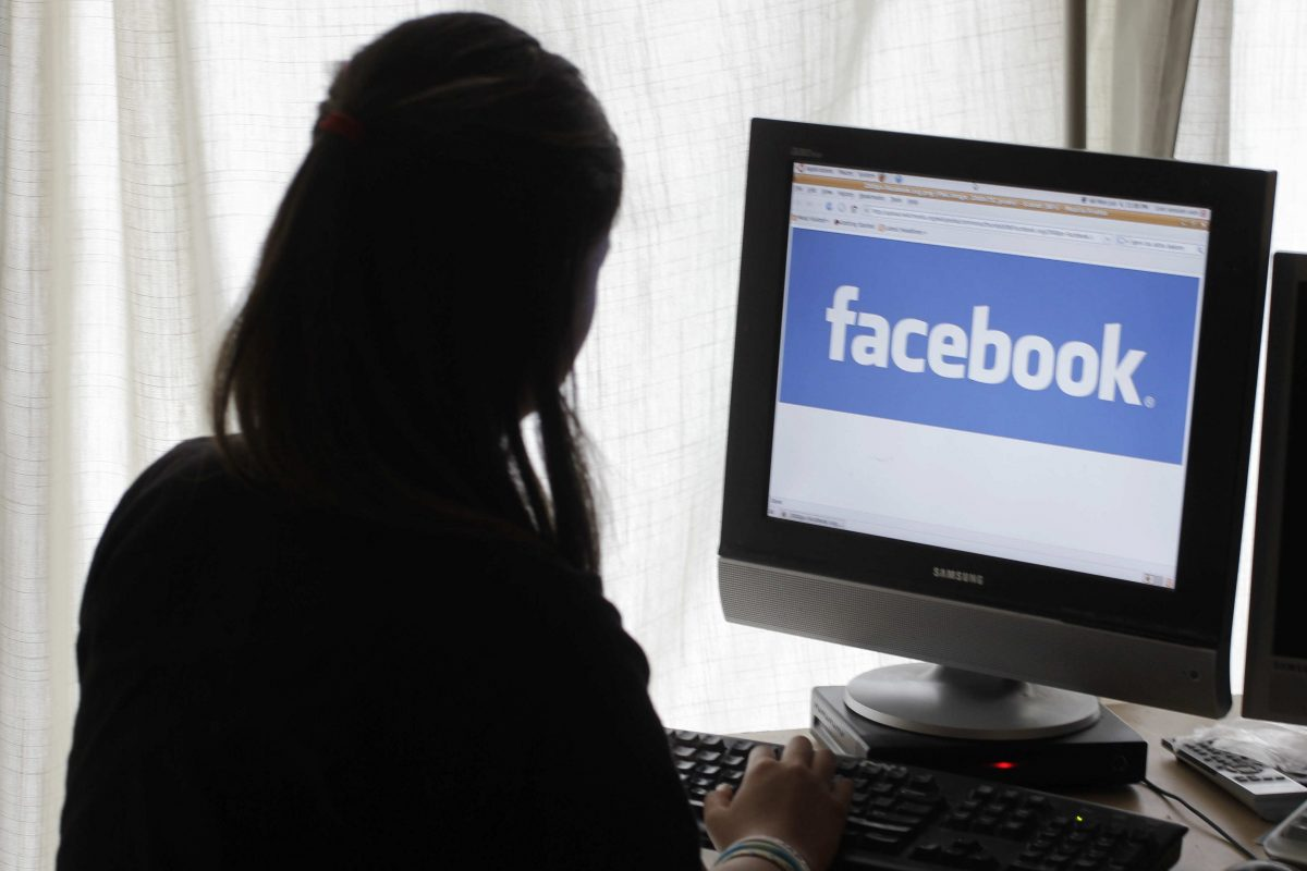 A girl looks at Facebook on her computer in Palo Alto, Calif., in a 2012 file photo. This weekend, Facebook banned the high-profile data firm Cambridge Analytica — paid more than $6 million by President Trump's 2016 campaign — after a joint New York Times/Guardian probe revealed the improper harvesting of data from an estimated 50 million users of the platform.