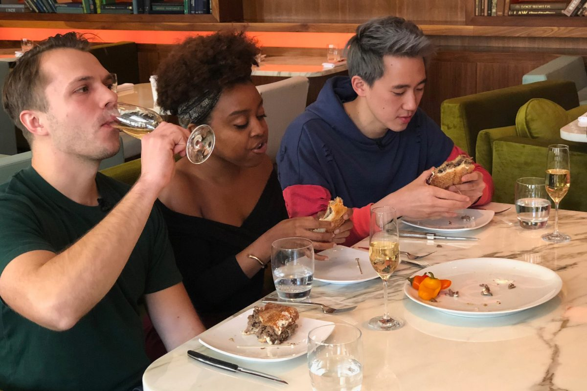 """Andrew Ilnyckyj (left), Philly comedian Quinta Brunson, and Steven Lim taping an episode of the BuzzFeed series """"Worth It"""" at Barclay Prime steakhouse."""