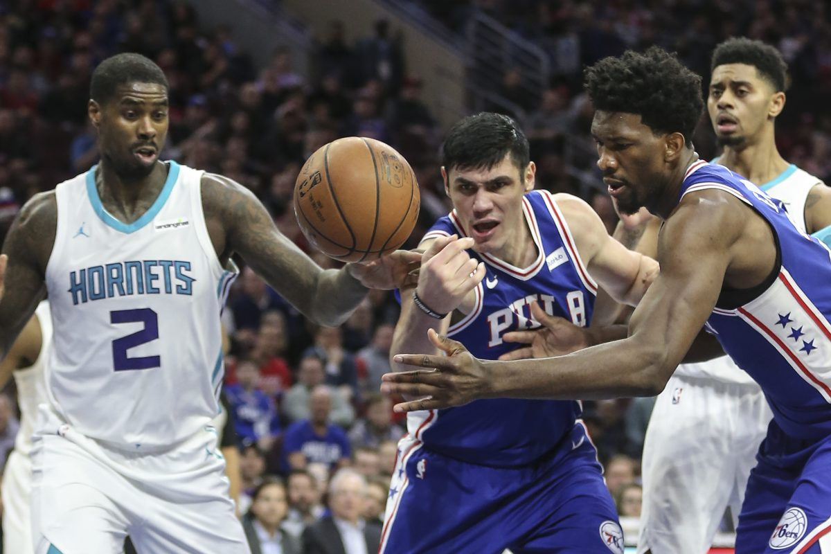 Sixers' Joel Embiid and Ersan Ilyasova try for the loose ball with Hornets' Marvin Williams during the 2nd quarter at the Wells Fargo Center in Philadelphia, Monday, March 19, 2018.