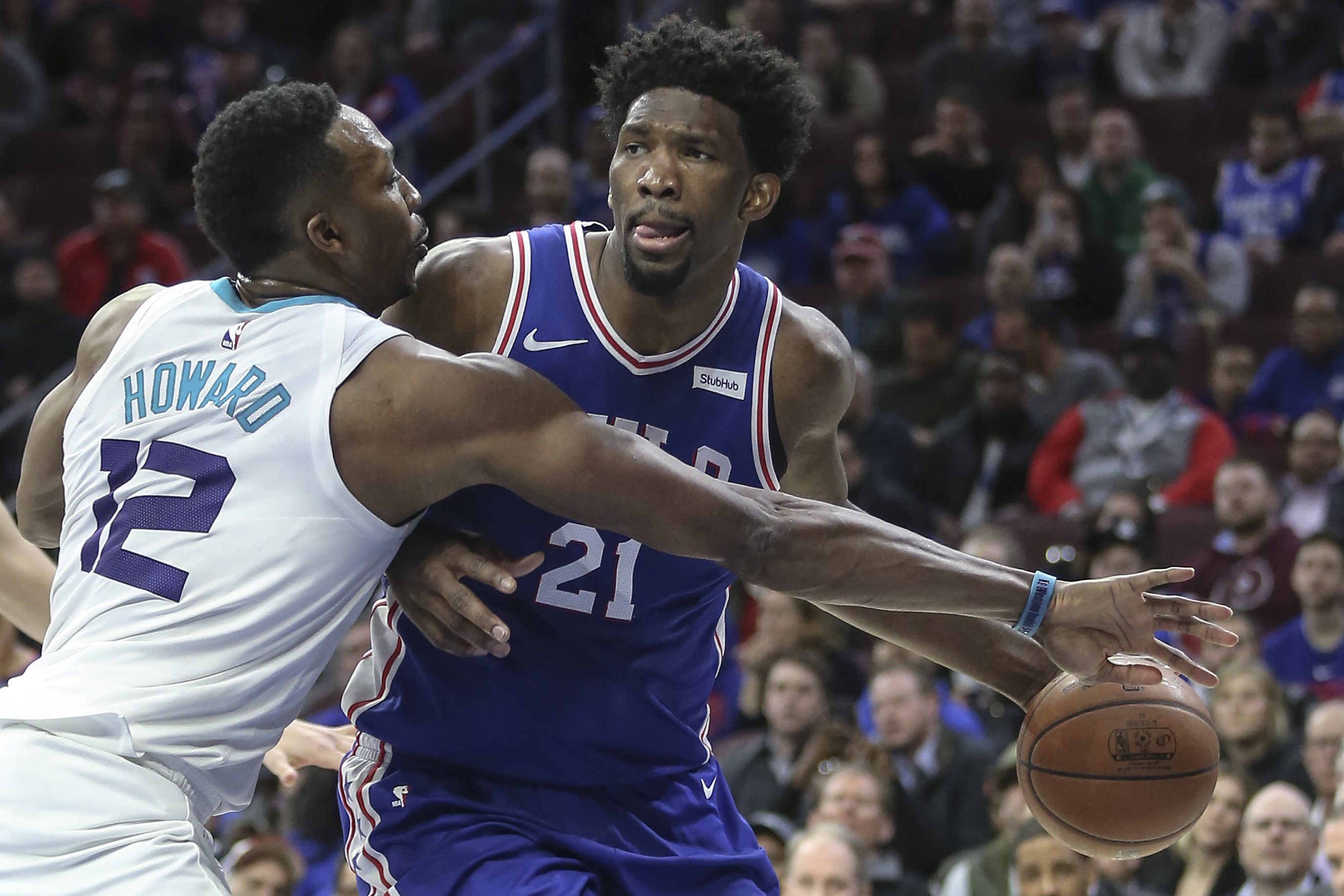 Joel Embiid keeps the ball from Dwight Howard of the Hornets during the third quarter.