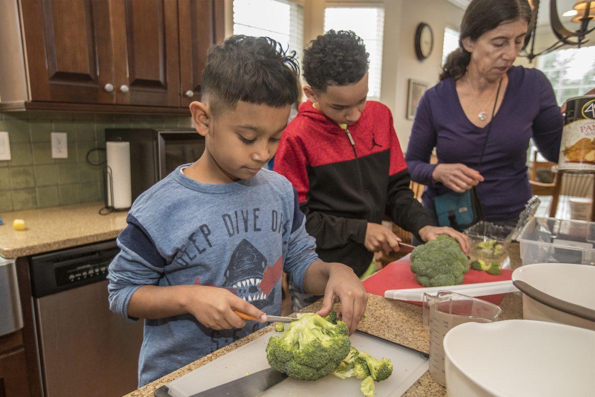Noah McBride (left), 11,  and Jaden Mosely, 10, cut up broccoli.