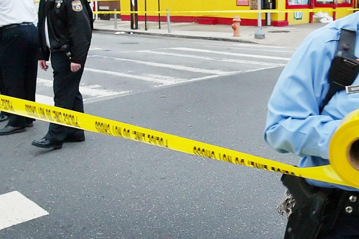 Philadelphia police run crime scene tape.