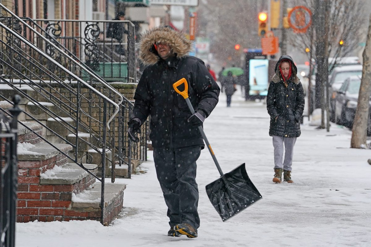 Josh Shaffer carries a snow shovel after clearing off his front steps on South Broad Street on Tuesday.