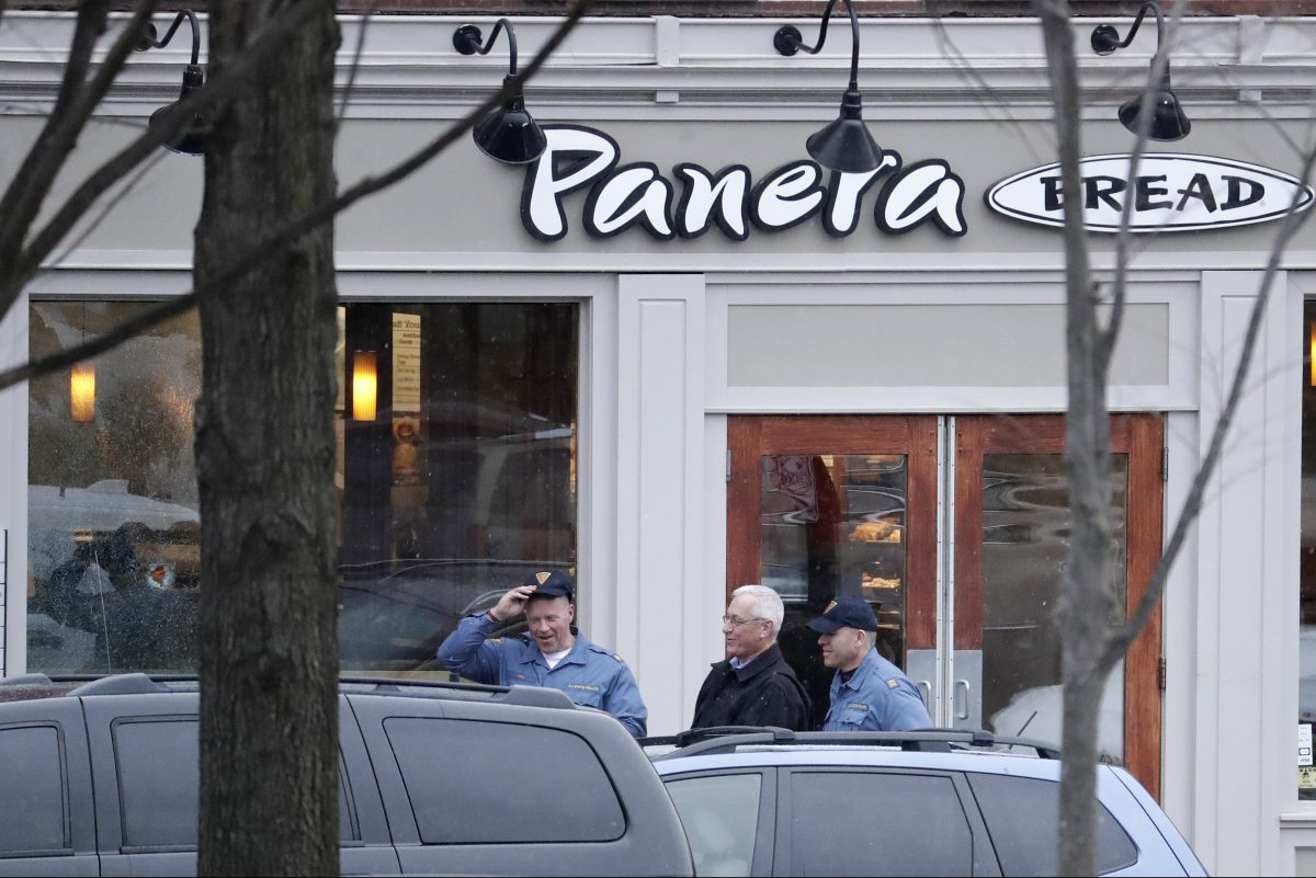 A hole is seen on the glass panel (far left) as New Jersey State Police officials walk out of a Panera Bread restaurant in Princeton, N.J., where an armed man was holed up across the street from Princeton University on Tuesday, March 20, 2018.