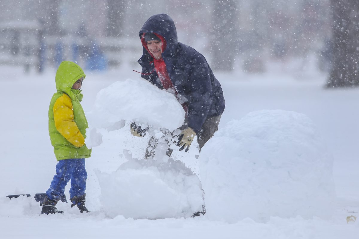 Juan Estrada and his 5-year-old son, Evan, build a snowman in Downingtown on Wednesday, March 21, 2018.