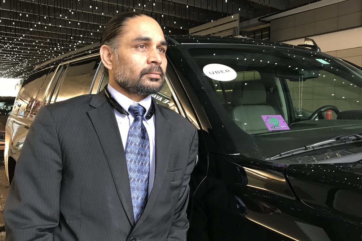 Virender Rana with the Chevrolet Suburban he drives for UberX and Uber Black