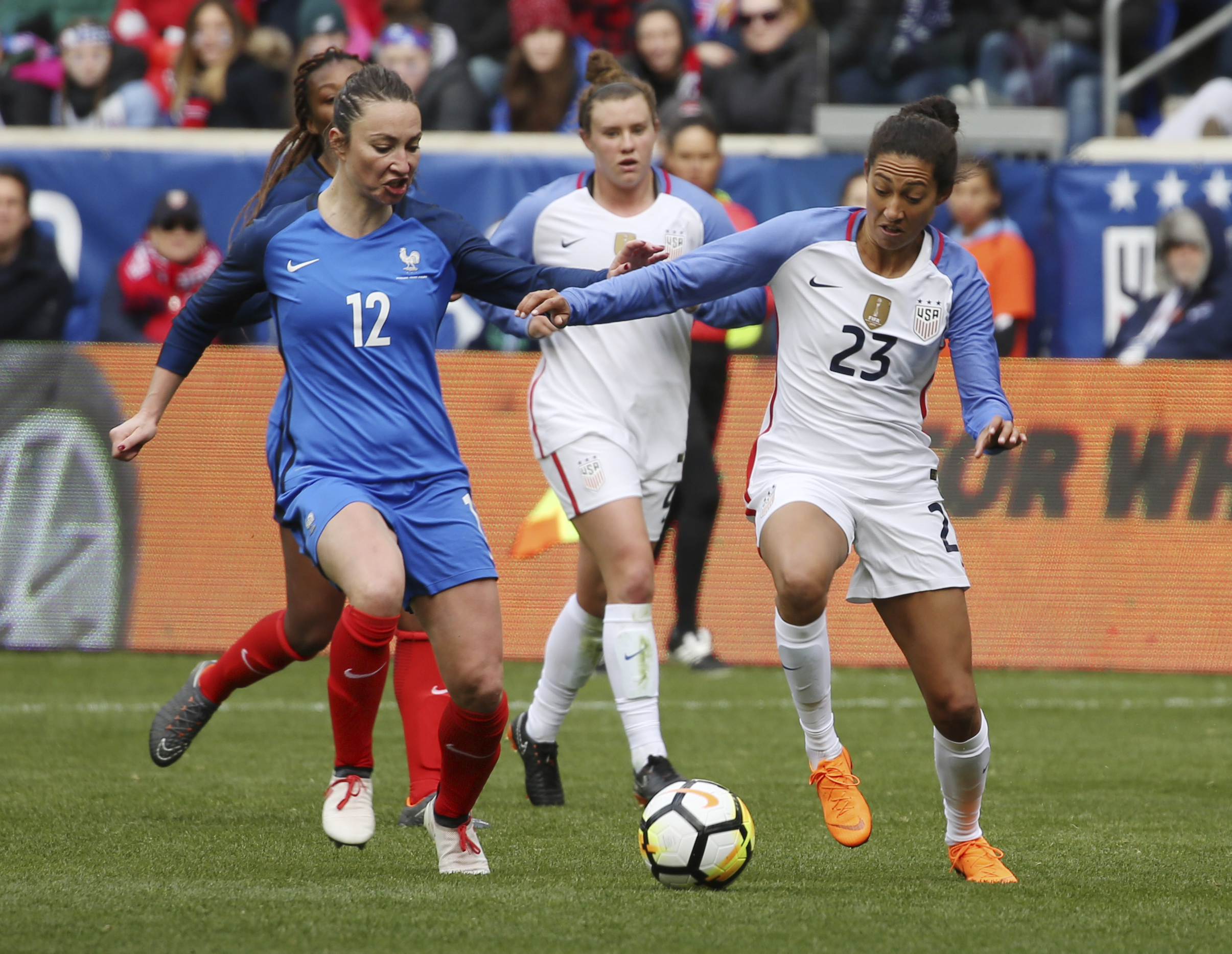 United States forward Christen Press (23) keeps the ball away from France midfielder Gaetane Thiney (12) during the second half of a SheBelieves Cup women´s soccer match, Sunday, March 4, 2018, in Harrison, N.J. The match ended in a 1-1 draw. (AP Photo/Steve Luciano)