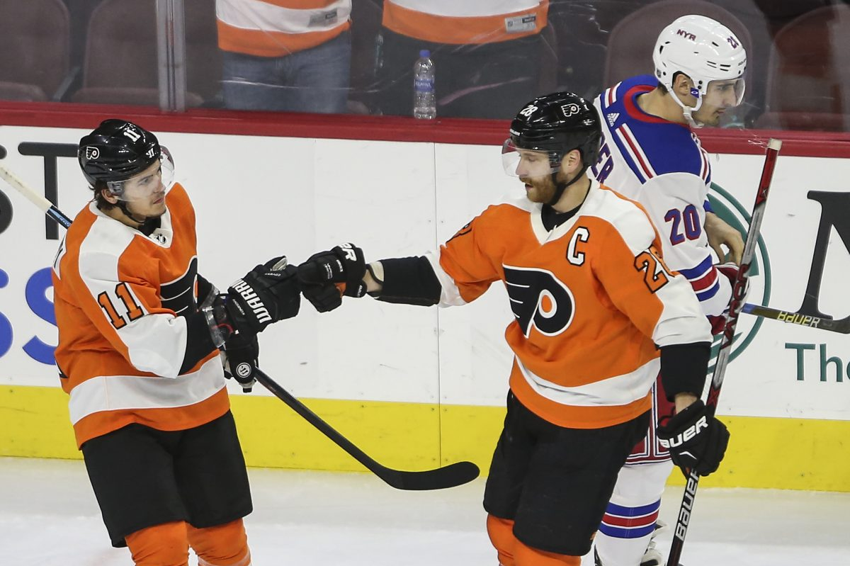 Flyers' Travis Konecny celebrates his goal with teammate Claude Giroux as Rangers' Chris Kreider skates by during the first period of the Flyers' win on Thursday.