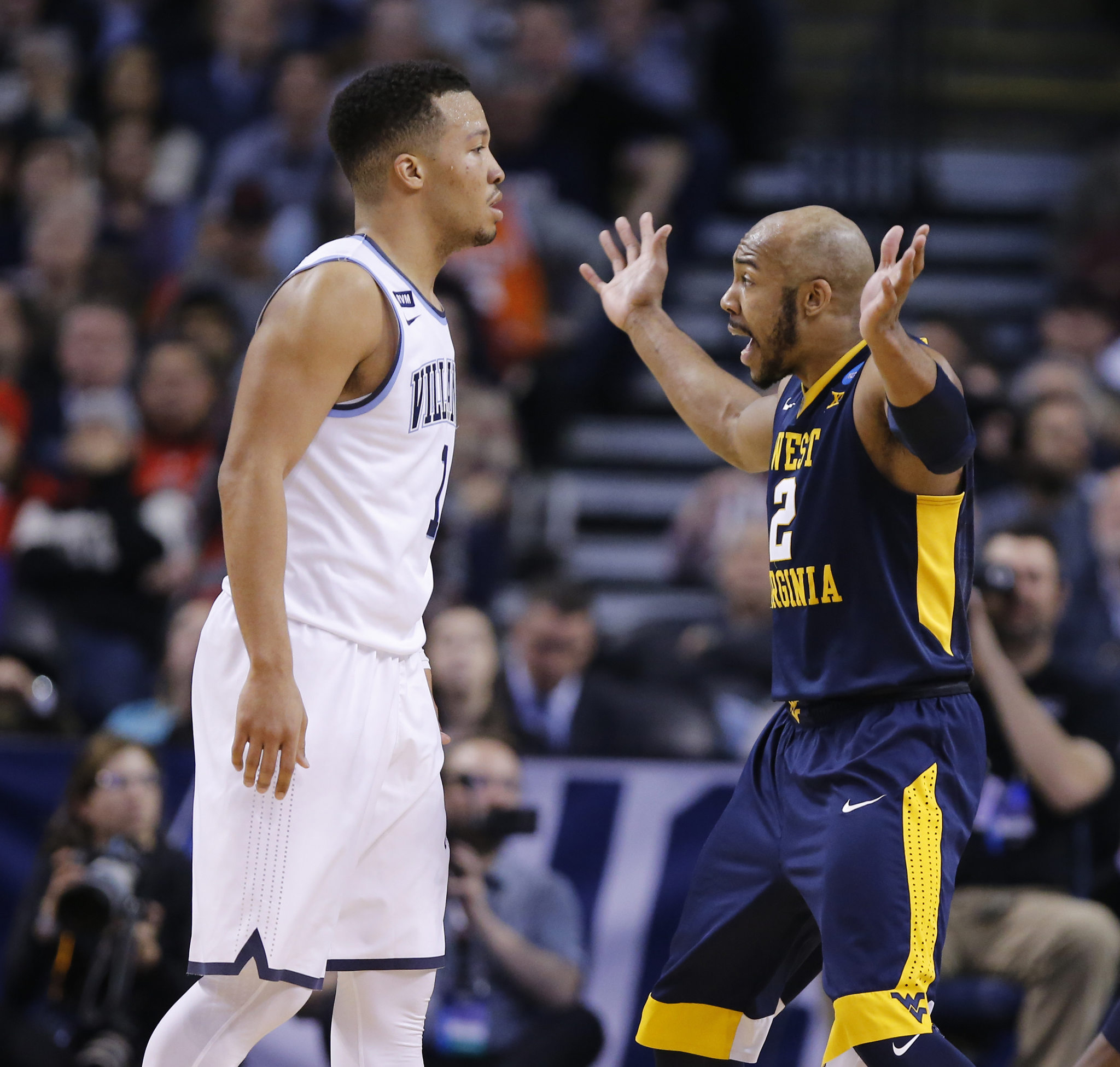 Jevon Carter, right, of West Virginia argues with a referee after being called for a foul while guarding Jalen Brunson, left of Villanova during the East Regionals of the NCAA Tournament at TD Garden on March 23, 2018.