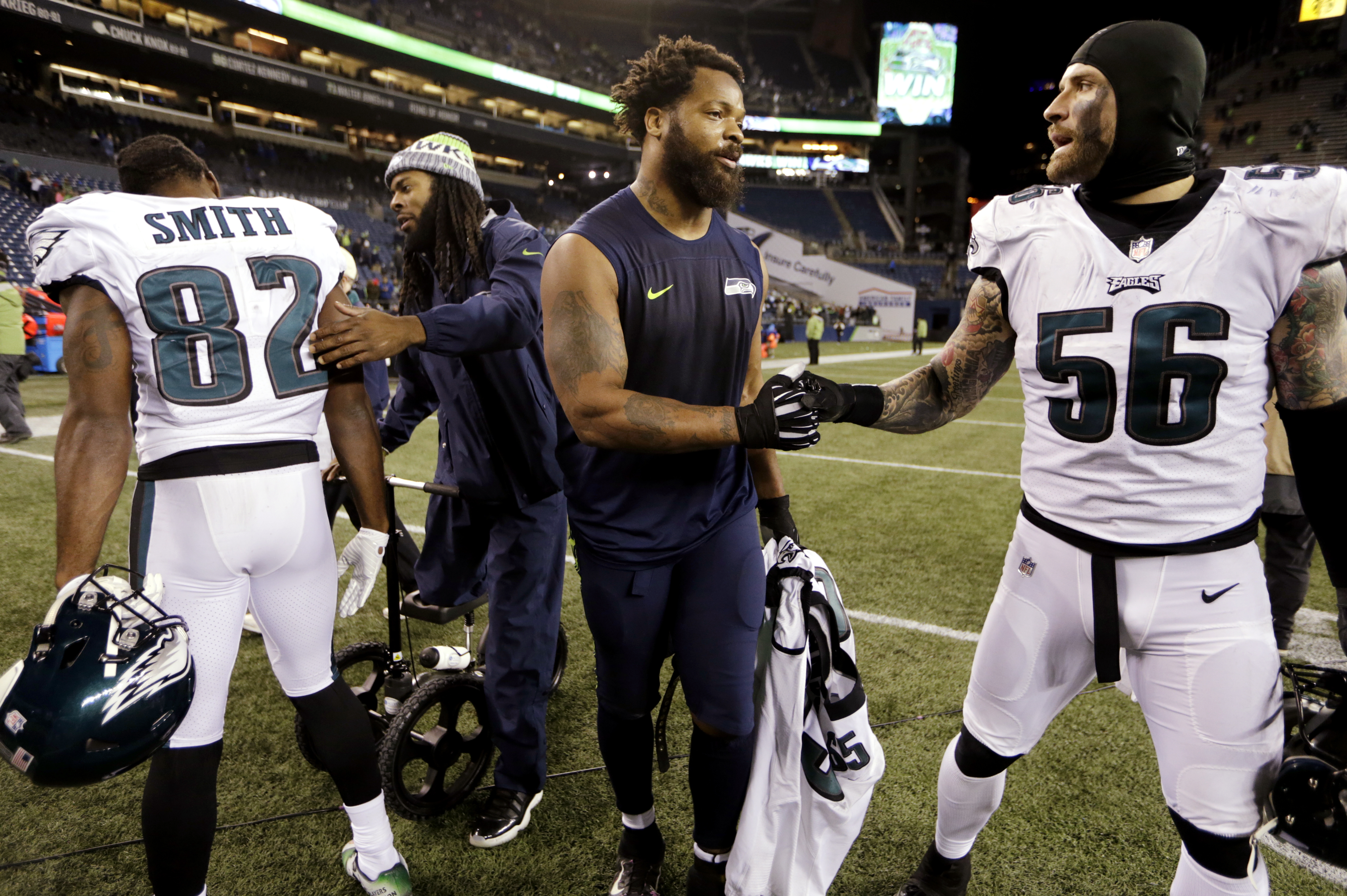 Seattle Seahawks Richard Sherman, second left, and Michael Bennett greet Philadelphia Eagles Torrey Smith (82) and Chris Long after an NFL football game, Sunday, Dec. 3, 2017, in Seattle.