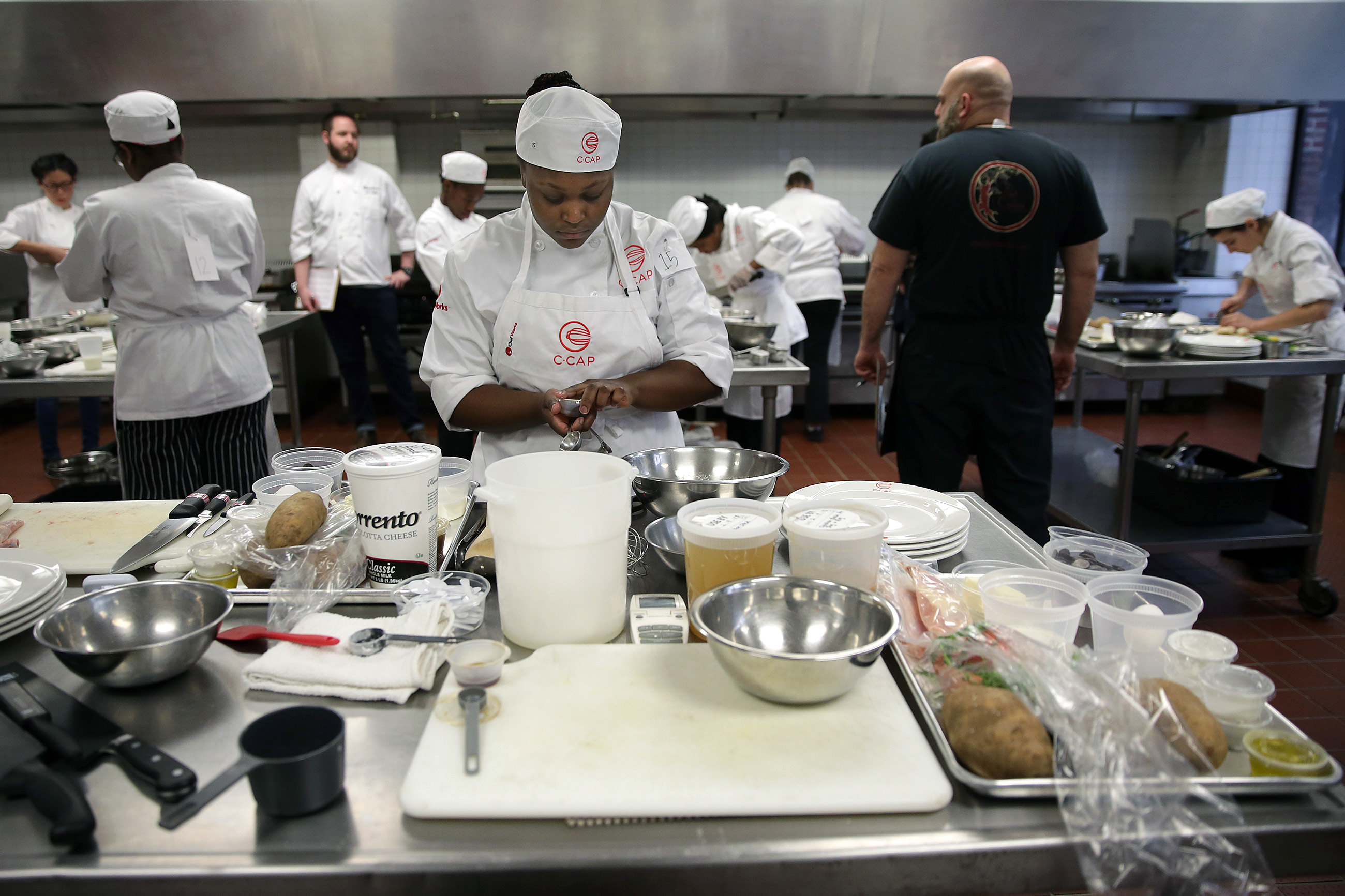 Martayia Hill, center, works on her dish during a competition sponsored by the Careers though Culinary Arts Program at The Art Institute of Philadelphia.