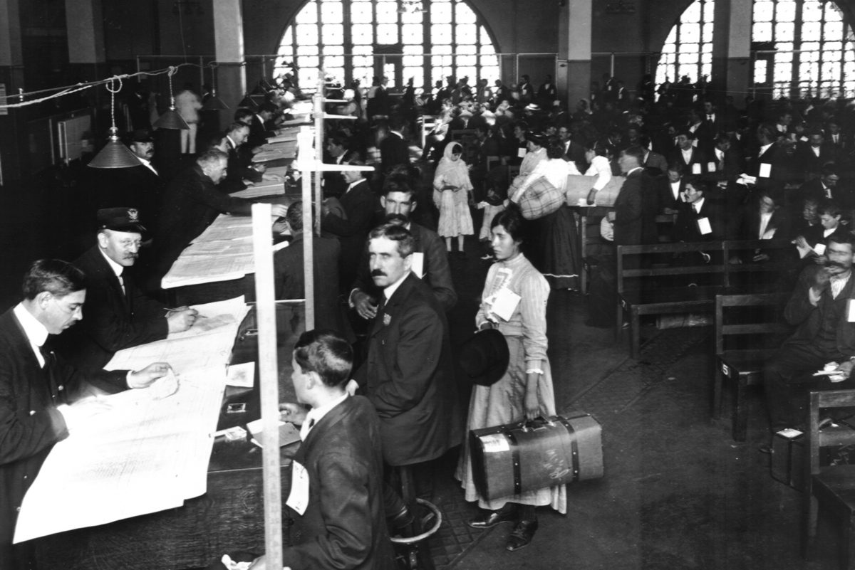 Immigrants arrive for  inspection at Ellis Island in the early 1900s