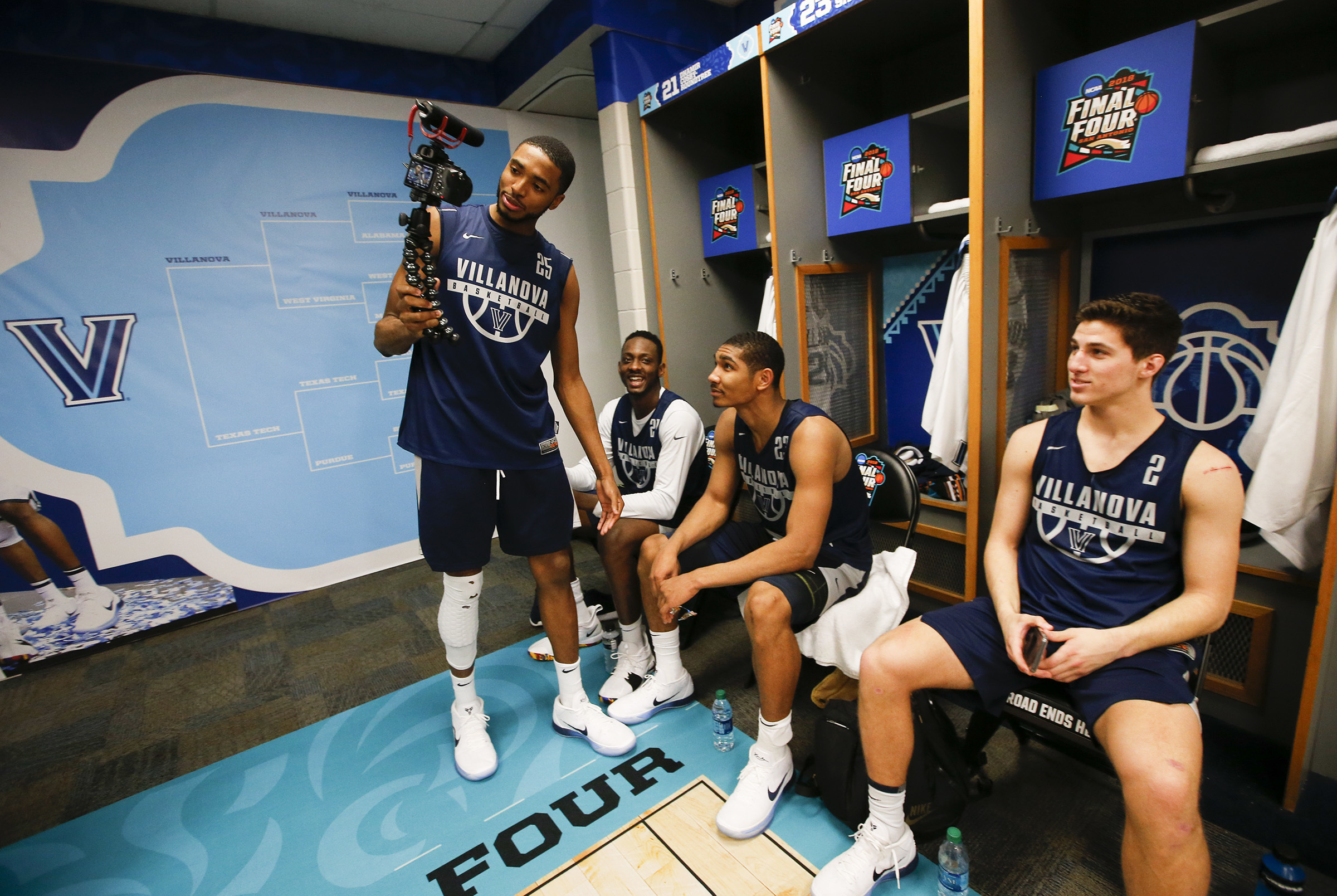 Villanova forward/guard Mikal Bridges uses a video camera to record a piece for the NCAA with teammates forward Dhamir Cosby-Roundtree, forward Jermaine Samuels and guard Collin Gillespie during a media availability after the team practiced on Thursday, March 29, 2018 at the Alamodome in San Antonio.