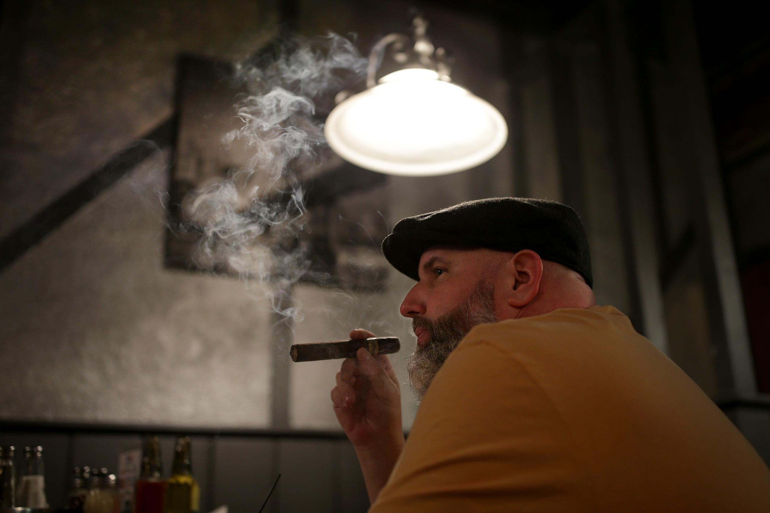 Joe Schwartz smokes a cigar at the Messina Club .