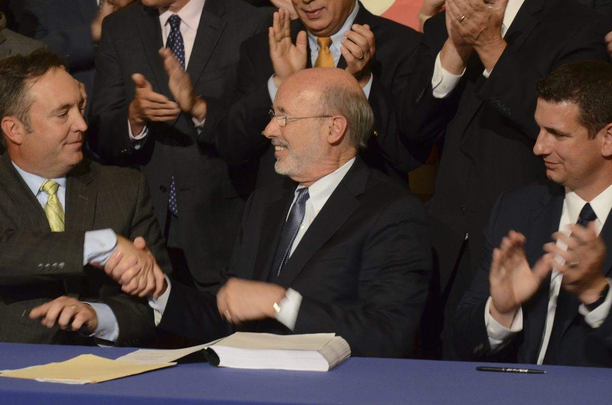 In happier times, Democratic Gov. Tom Wolf shakes hands with Senate Majority Leader Jake Corman (R., Centre) after signing legislation on June 12 to reduce long-term public pension costs. Looking on is House Majority Leader Dave Reed (R., Indiana).