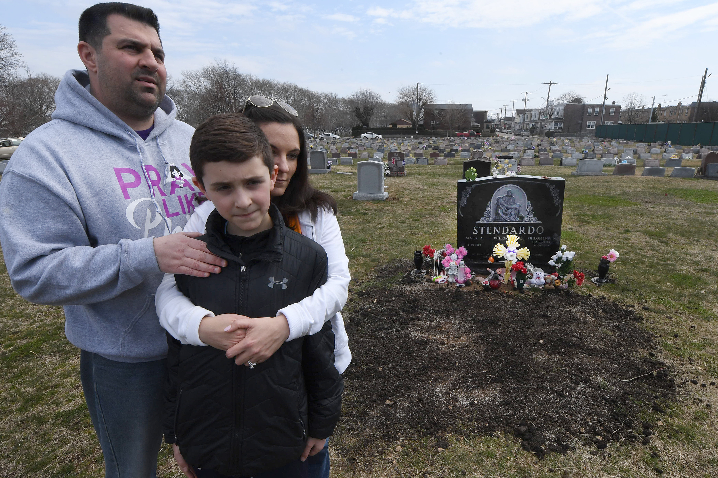 Mark Stendardo and Mina Carroll with son Mark near the grave of their daughter Philomena.