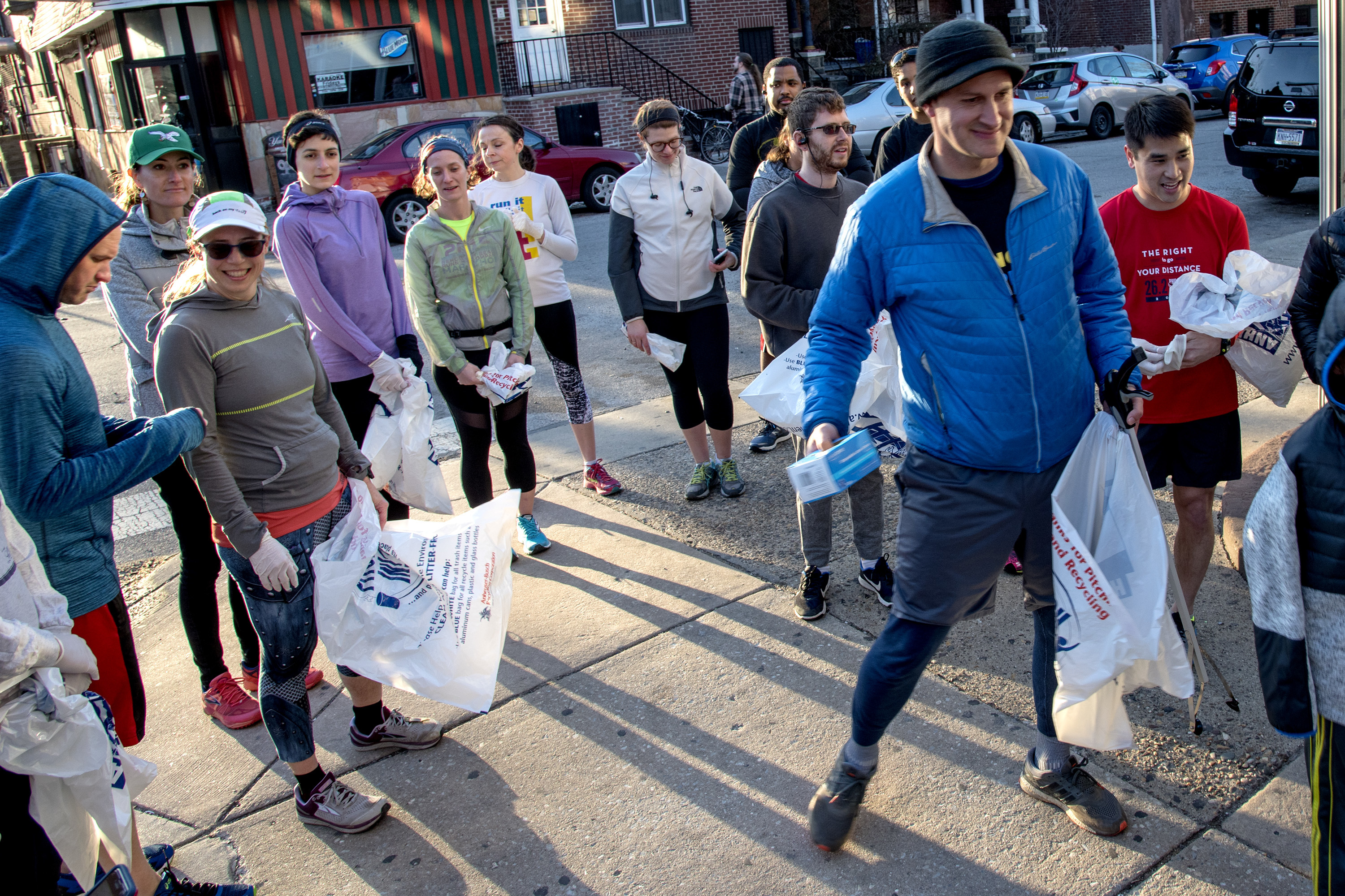 Dave Brindley (right) with Not in Philly, hands out gloves and trash bags before the West Philly Runners try out plogging ahead of Philly Plogging week April 9-15. TOM GRALISH / Staff Photographer