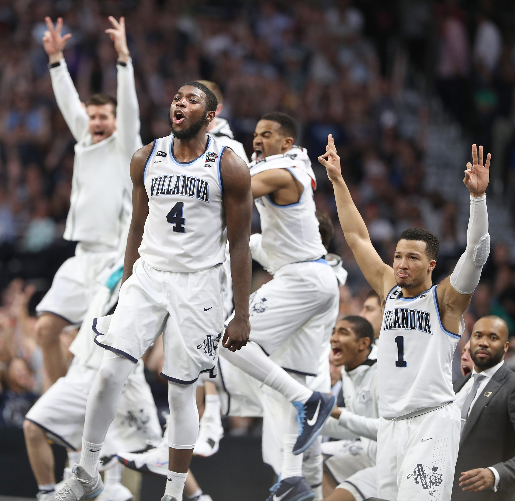 Eric Paschall, center, and Jalen Brunson, right, and the Villanova bench celebrate after a Donte DiVincenzo 3-pointer against Michigan during the 2nd half of the National Championship game of the NCAA Tournament at the Alamodome on April 2, 2018.