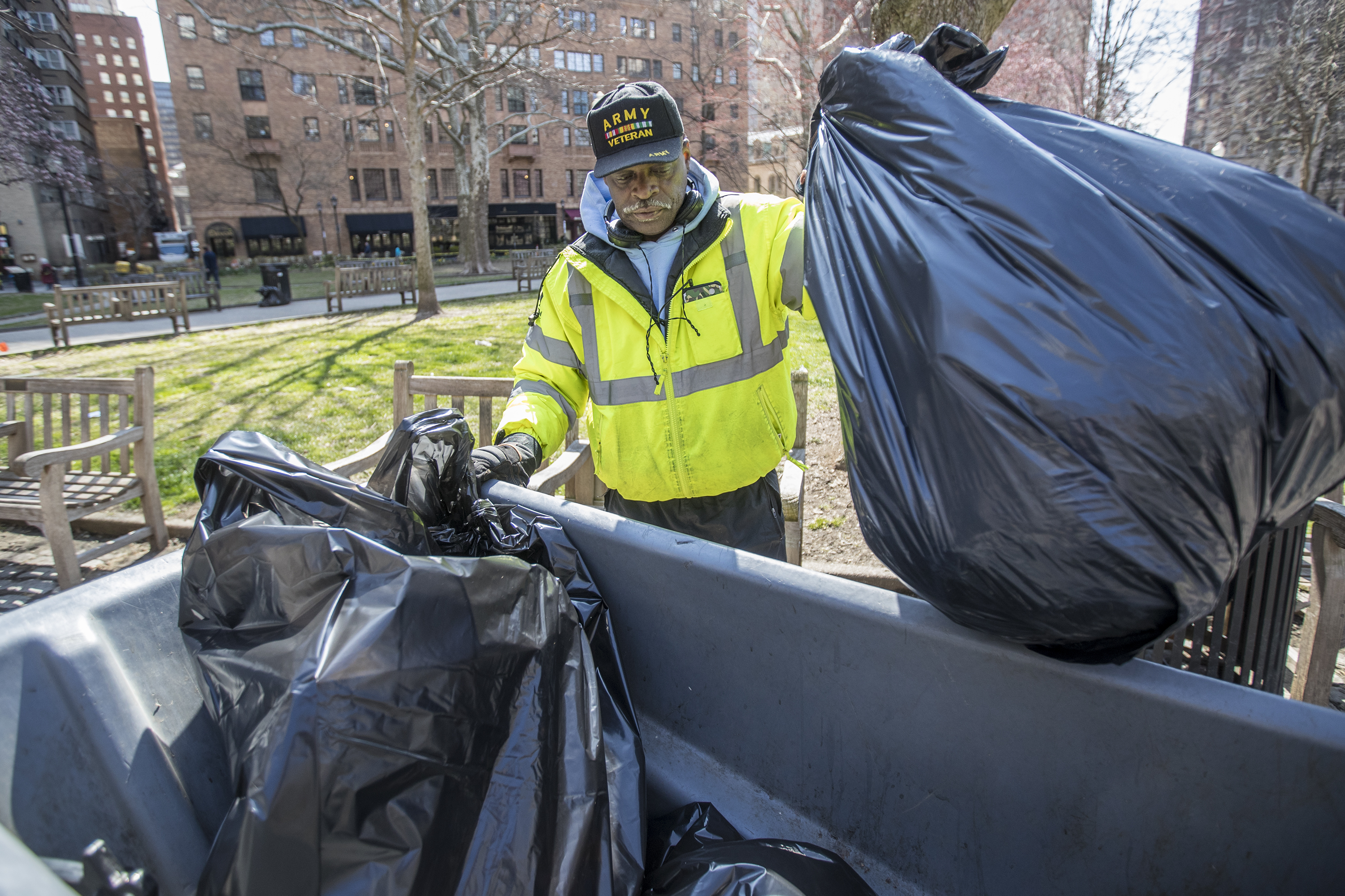 Carlos Rowland loads up a bag of garbage from one of the 89 garbage cans at the park as part of his daily duties.