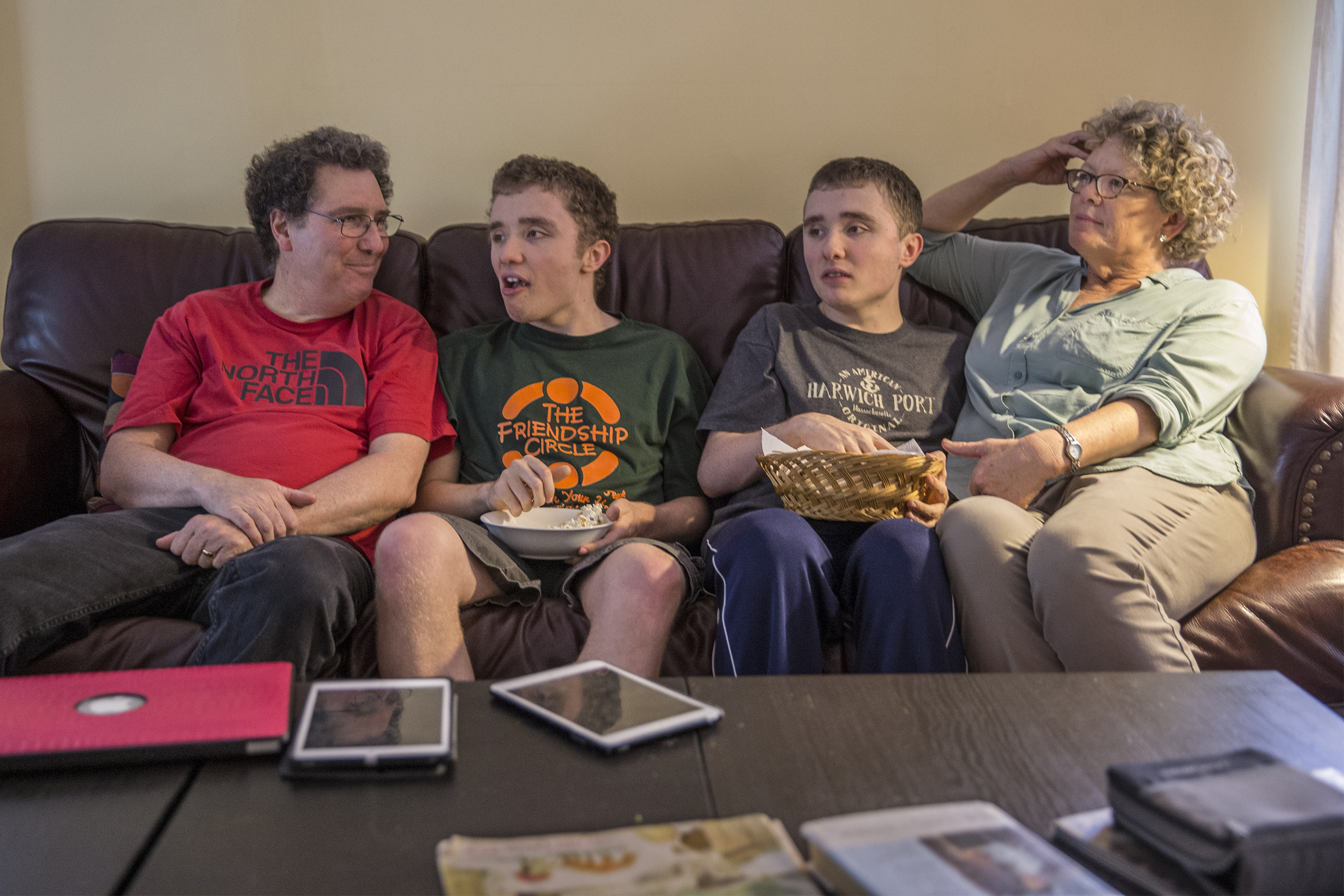 "Gary Berstein, left, and his wife, Sheila Kineke, right, sit with their severely intellectually disabled twins Lewis, left, and Andrew, right, who are waiting for benefits to fund their care. The family was profiled in ""Falling Off the Cliff."""